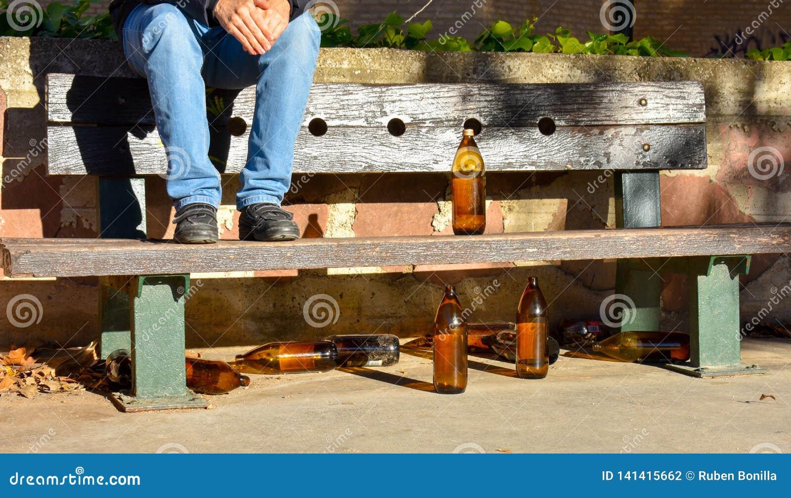 O homem sentou-se em um banco com muitas garrafas alaranjadas grandes da cerveja feitas do vidro completamente vazio no parque de