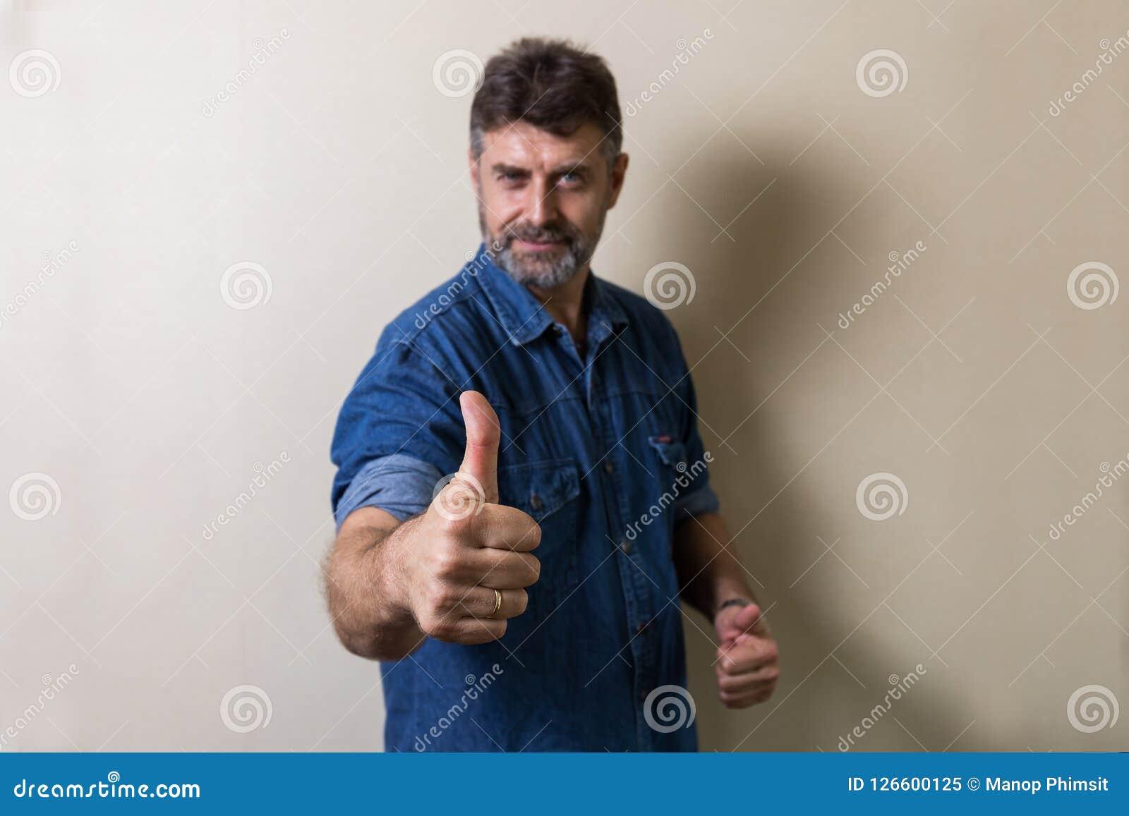 O homem superior dos Caucasians faz os polegares acima