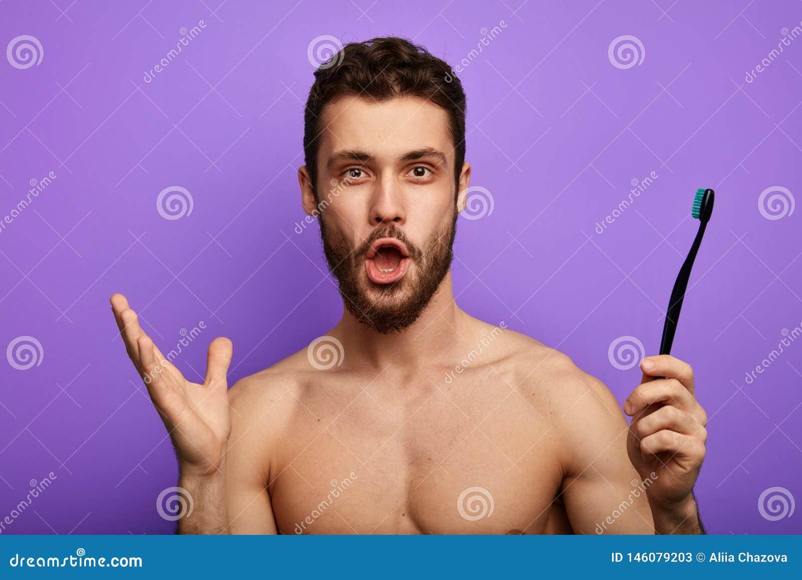 O homem surpreendido com a boca extensamente aberta, olhares fixos na câmera, guarda a escova de dentes à disposição
