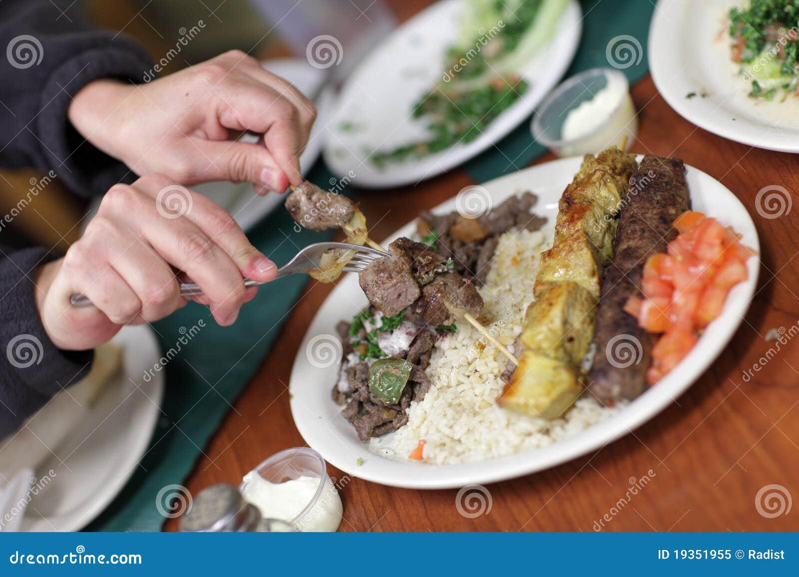 O homem toma a parte de kebab