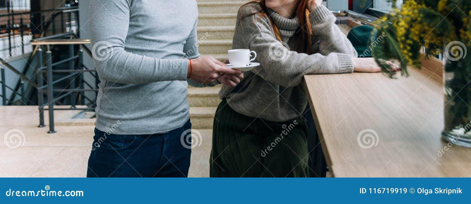 O homem trouxe o café, chá à menina que se senta na tabela quer obter familiar