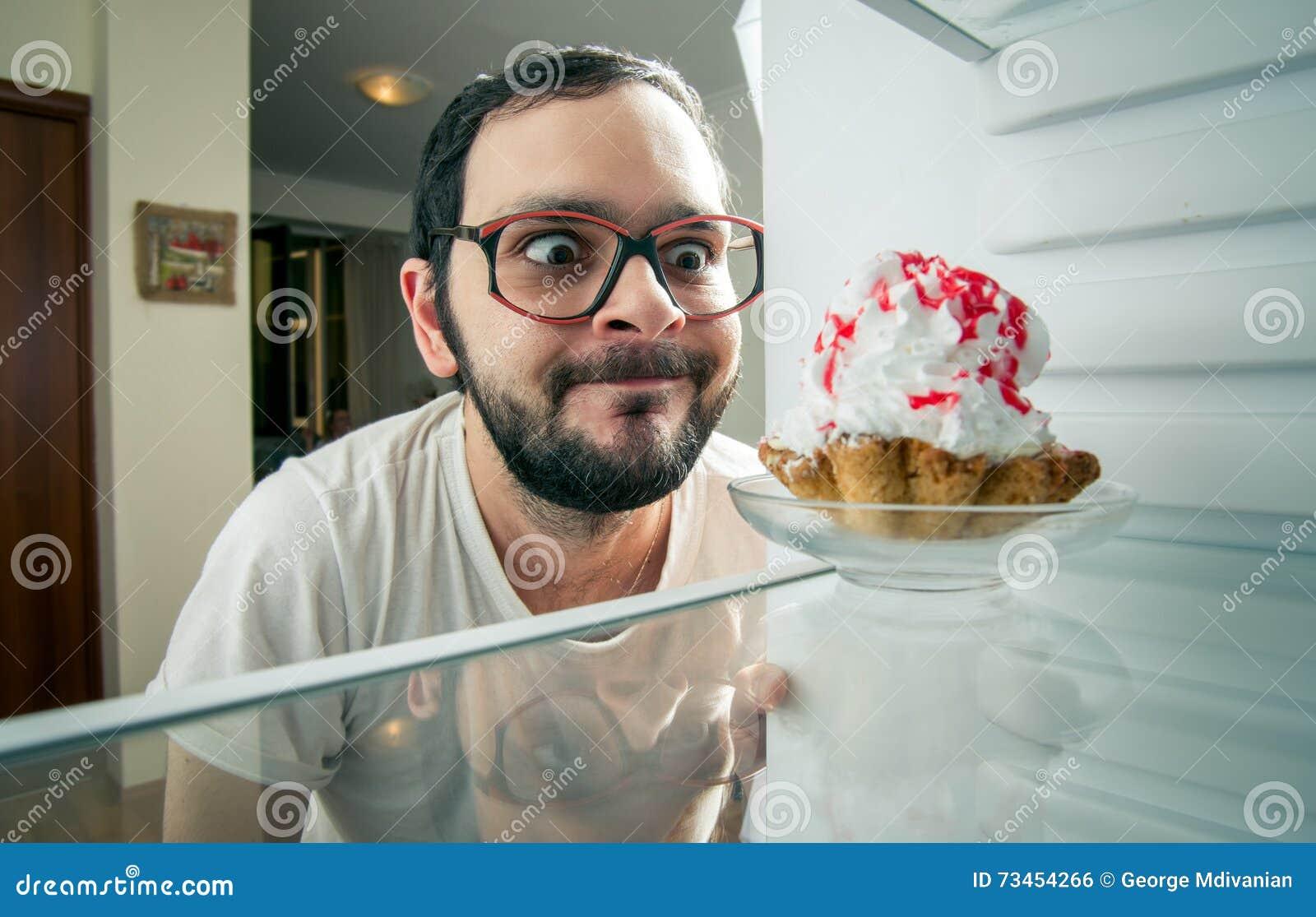 O homem vê o bolo doce no refrigerador