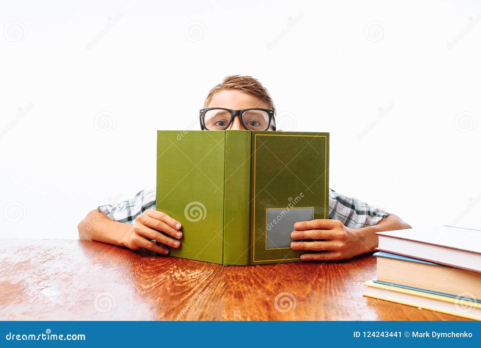 O indivíduo adolescente caiu assento adormecido com livros, estudante que dorme na mesa no estúdio no fundo branco