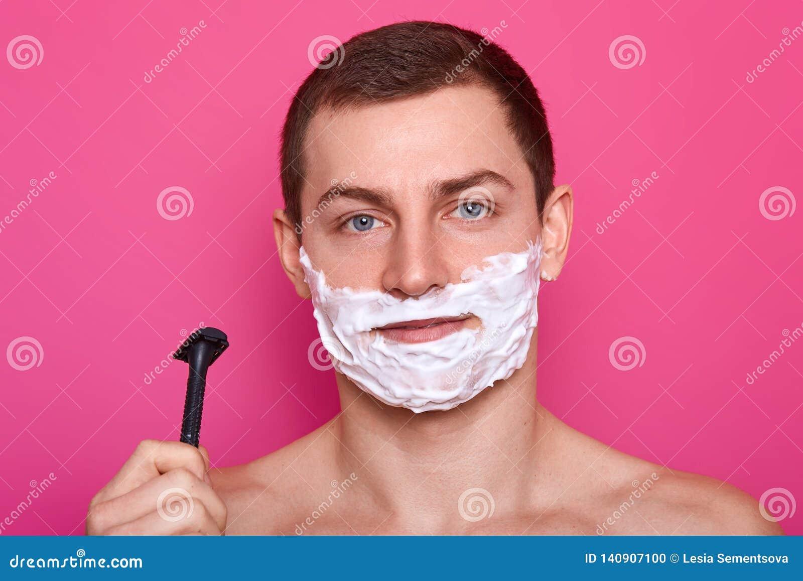 O indivíduo atrativo novo pronto para barbear com a lâmina no banheiro, põe o creme sobre a cara, sobre o fundo cor-de-rosa Homem