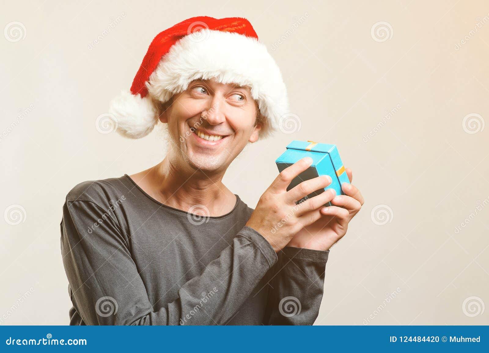 O indivíduo engraçado com chapéu do Natal guarda o presente pequeno Feriado do ano novo Natal, x-mas, conceito dos presentes do i
