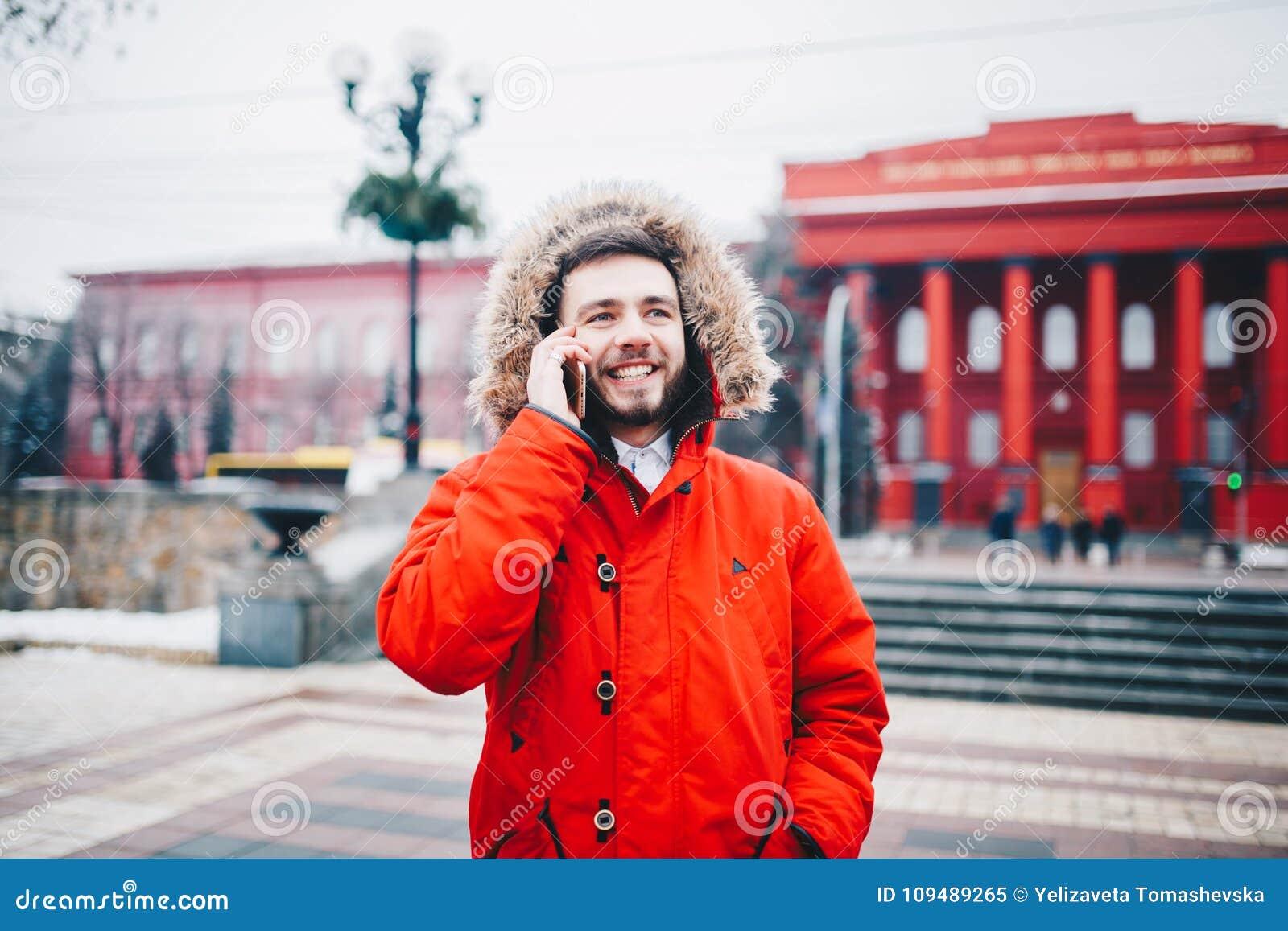 O indivíduo novo com barba e o revestimento vermelho na capa um estudante usa o telefone celular, realiza em sua mão perto da cab