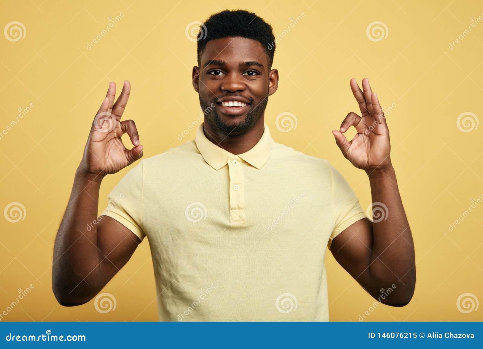 O indivíduo positivo mostra o gesto APROVADO em um fundo amarelo