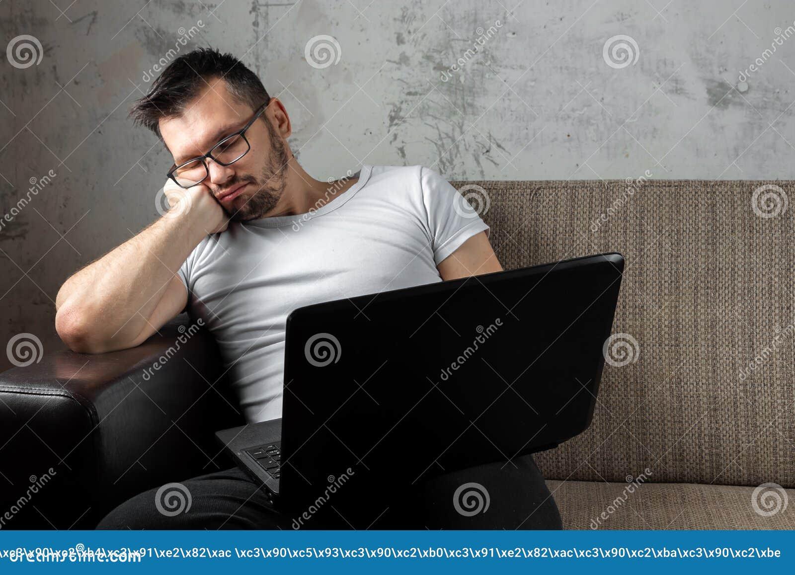 O indiv?duo na camisa branca que senta-se no sof?, caiu adormecido no trabalho em um port?til O conceito da pregui?a, apatia