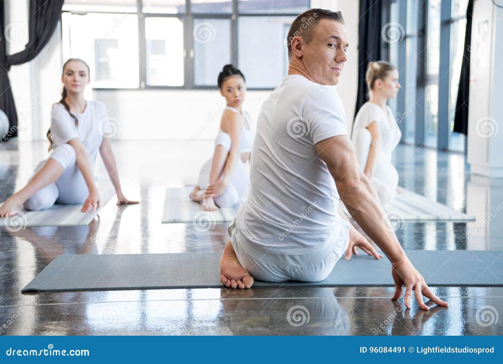 O instrutor e seu grupo que praticam a meia torção espinal levantam no gym
