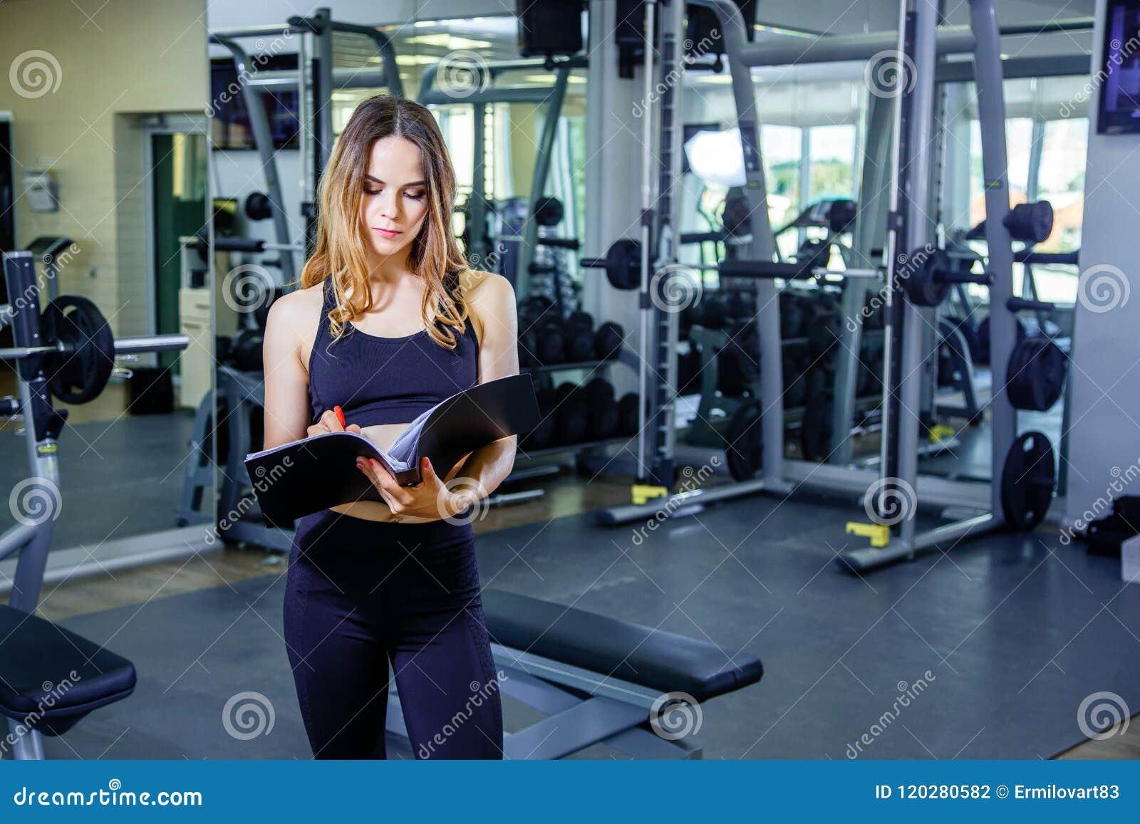 O instrutor pessoal da jovem mulher escreve o plano de treinamento em um caderno