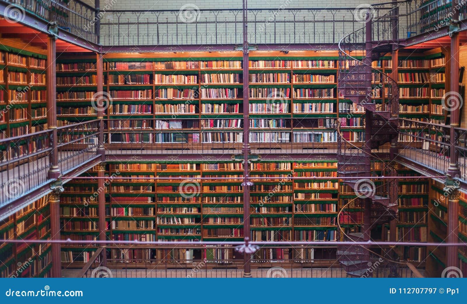 O interior antigo velho da biblioteca, teto registra, janelas, estante