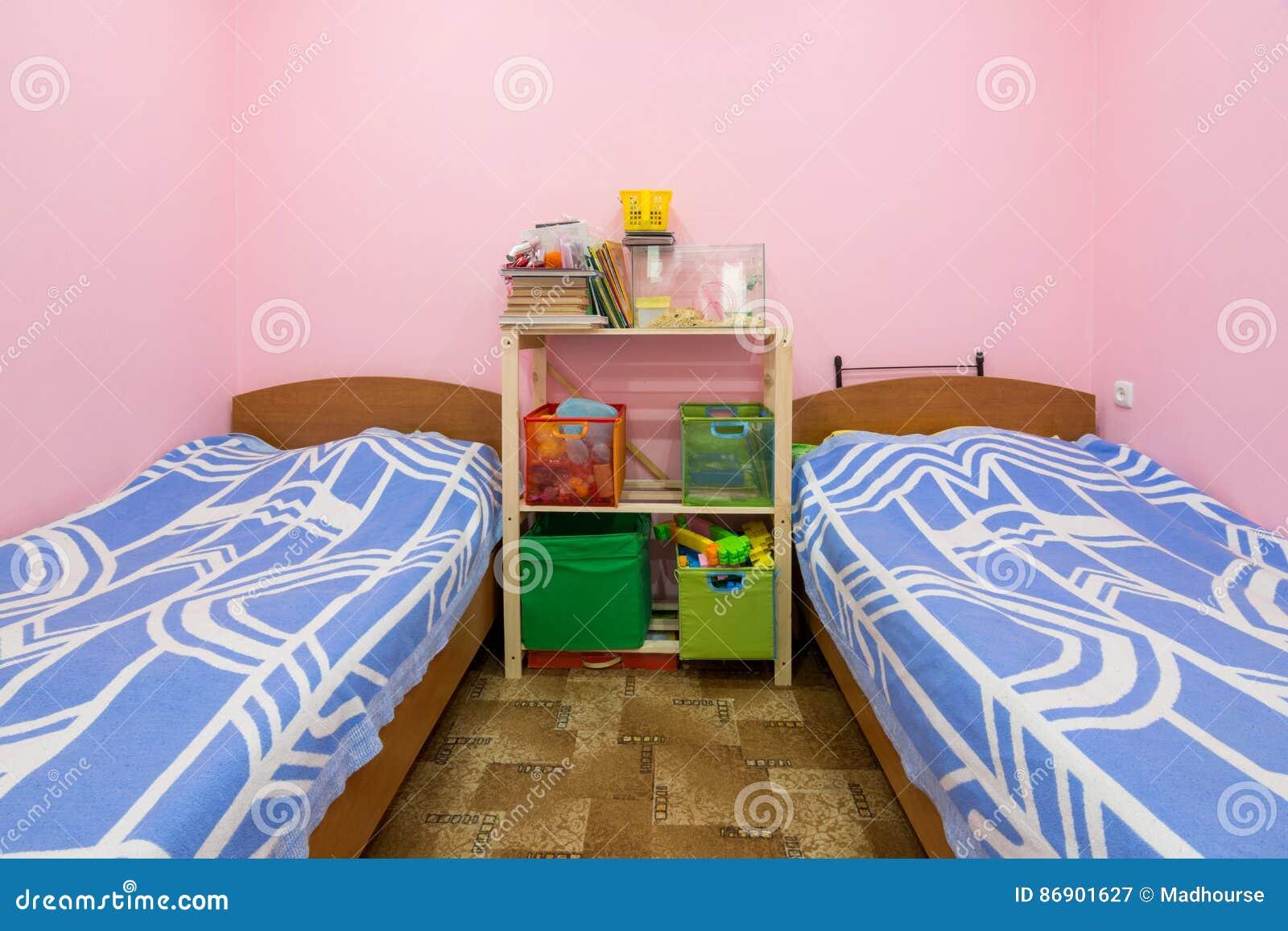 O interior da sala pequena do dormitório com duas camas e uma cremalheira caseiro no meio