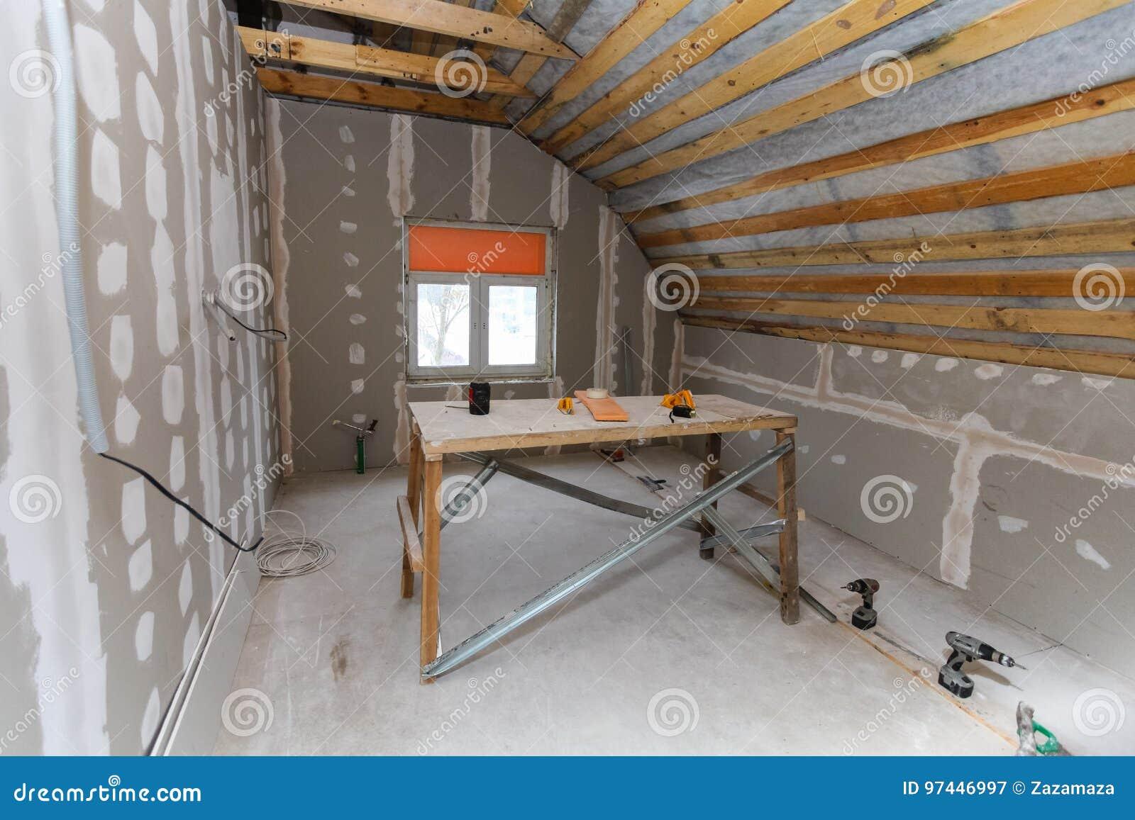O interior do apartamento da sala com nova janela e materiais casa-fez o andaime, brocas, nível durante na renovação