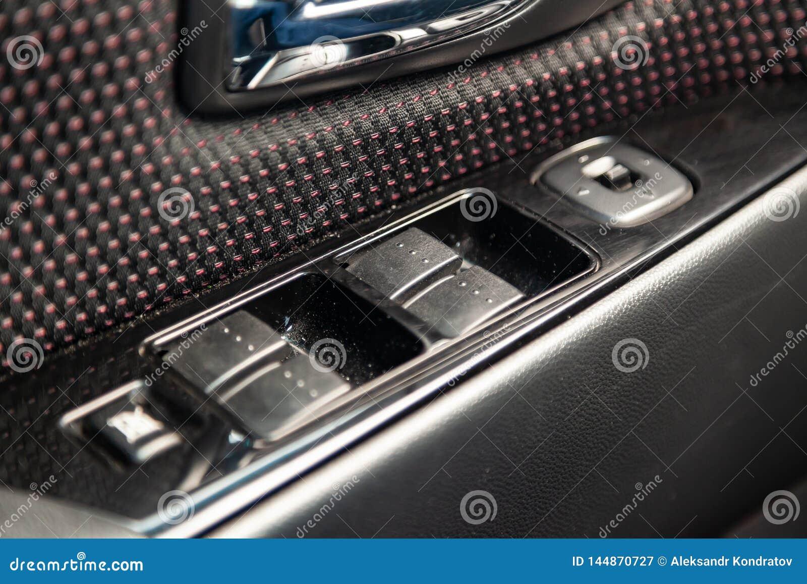 O interior do carro com uma vista do painel, das janelas e dos botões do espelho com guarnição cinzenta e vermelha da luz -