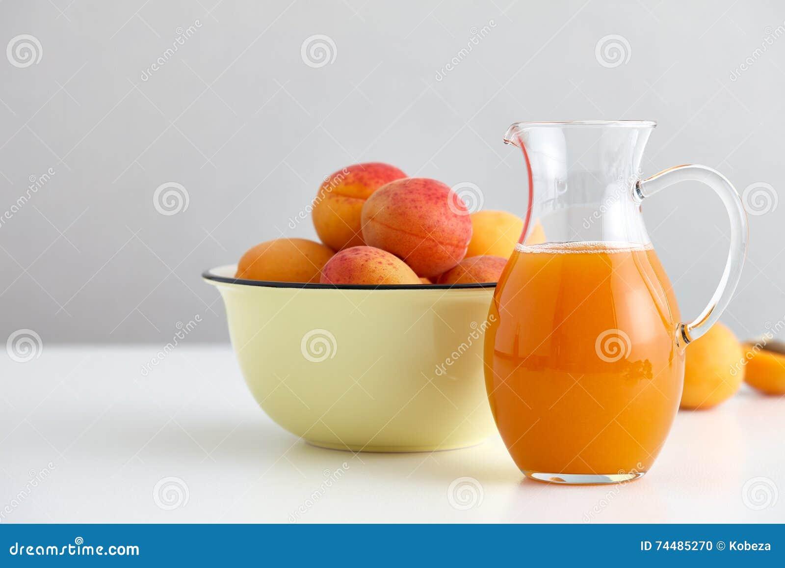 O jarro de vidro com suco fresco e os abricós maduros rolam
