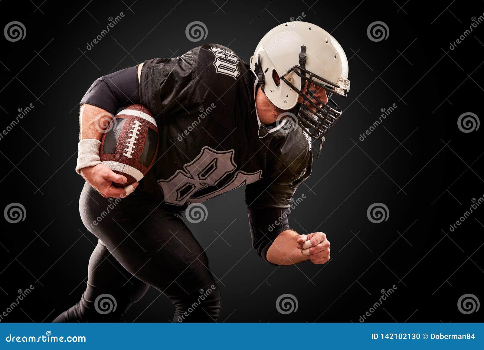 O jogador de futebol americano no uniforme escuro com a bola está preparando-se para atacar em um fundo preto