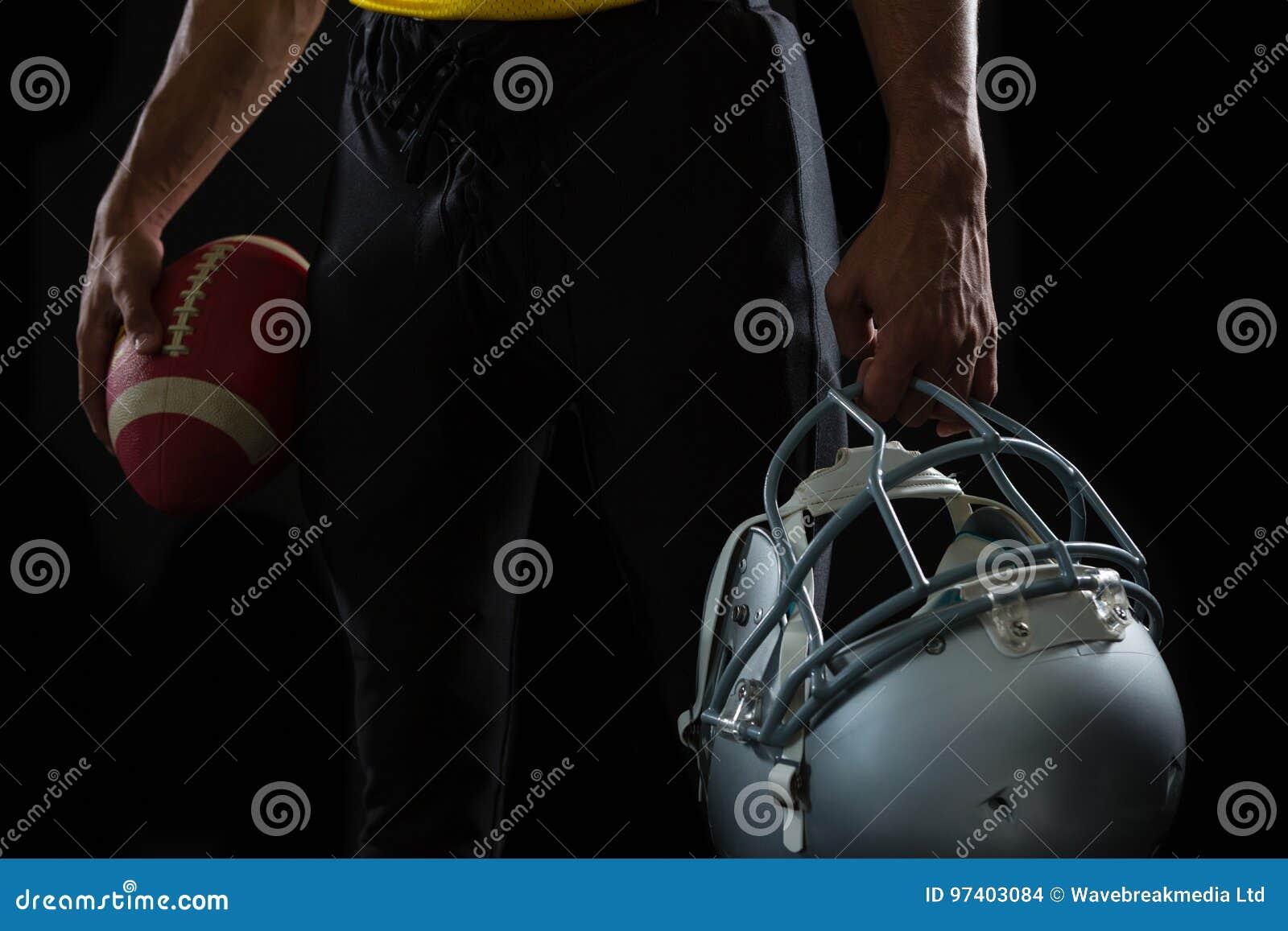 1003e363e A seção meados de do jogador de futebol americano que guarda uma bola e a  cabeça alinham