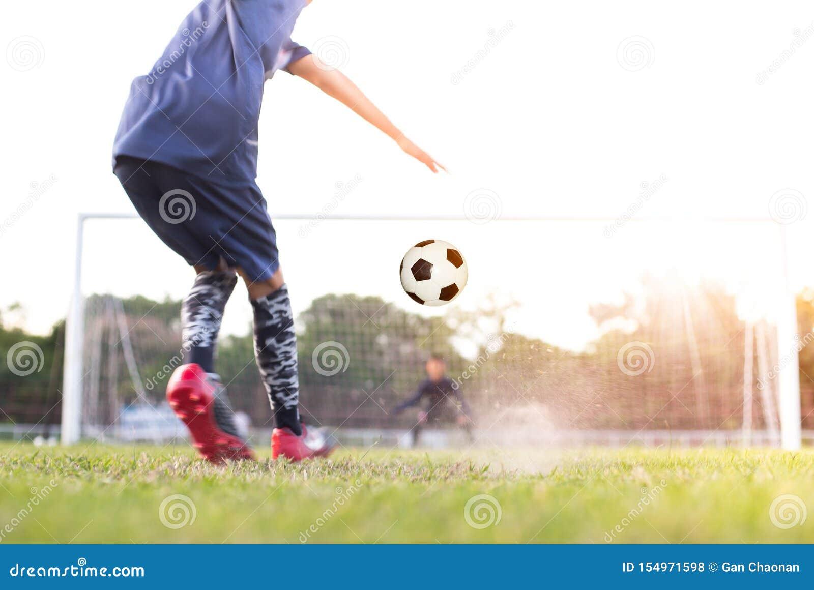 O jogador de futebol do futebol da equipe consegue a bola livrar o pontapé ou o pontapé de grande penalidade