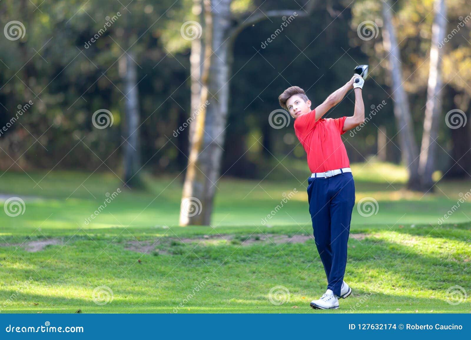 O jogador de golfe novo bate um motorista disparado do T em um cour do golfe