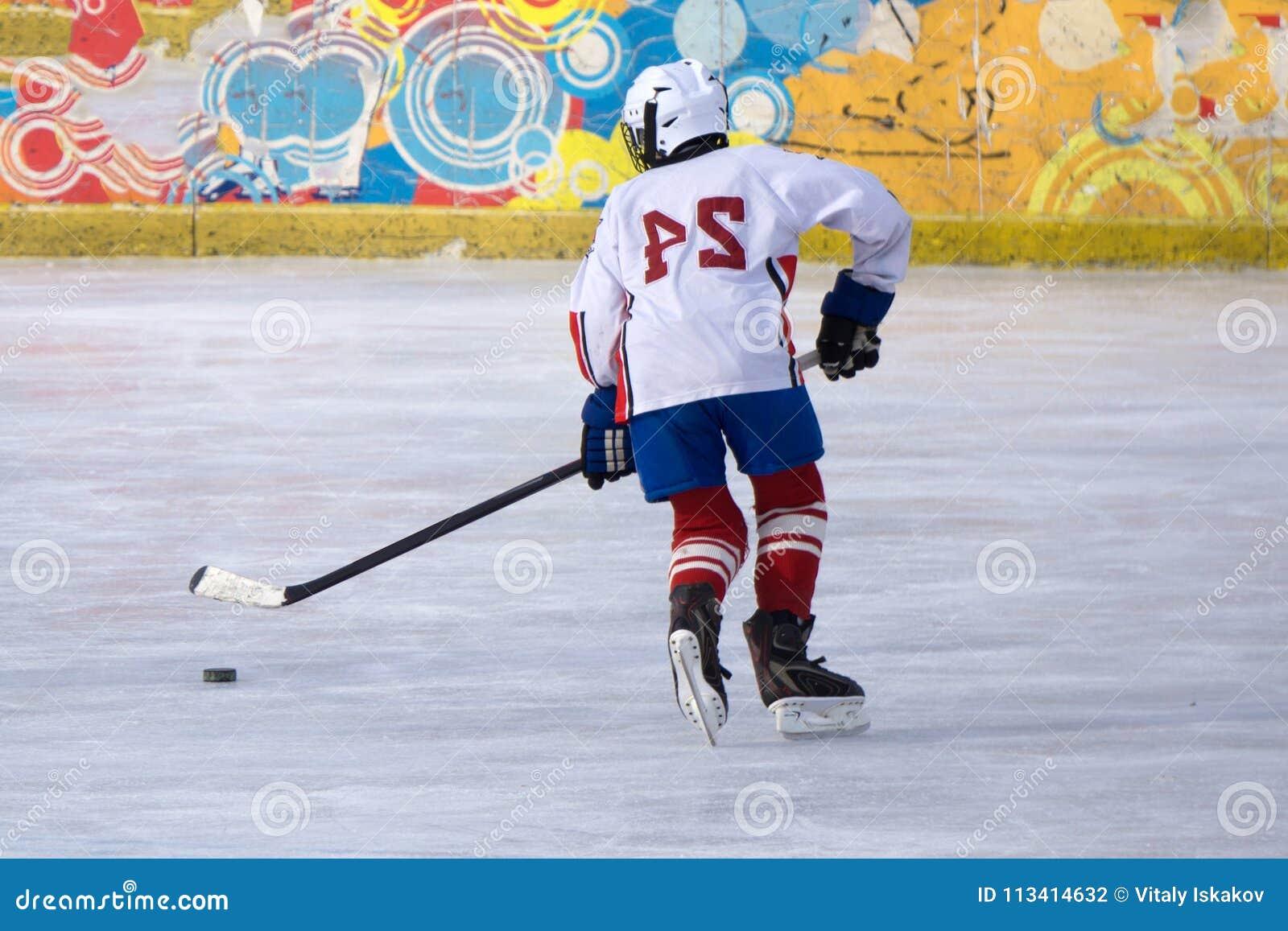 O jogador de hóquei com um disco no gelo da lâmina move o gelo
