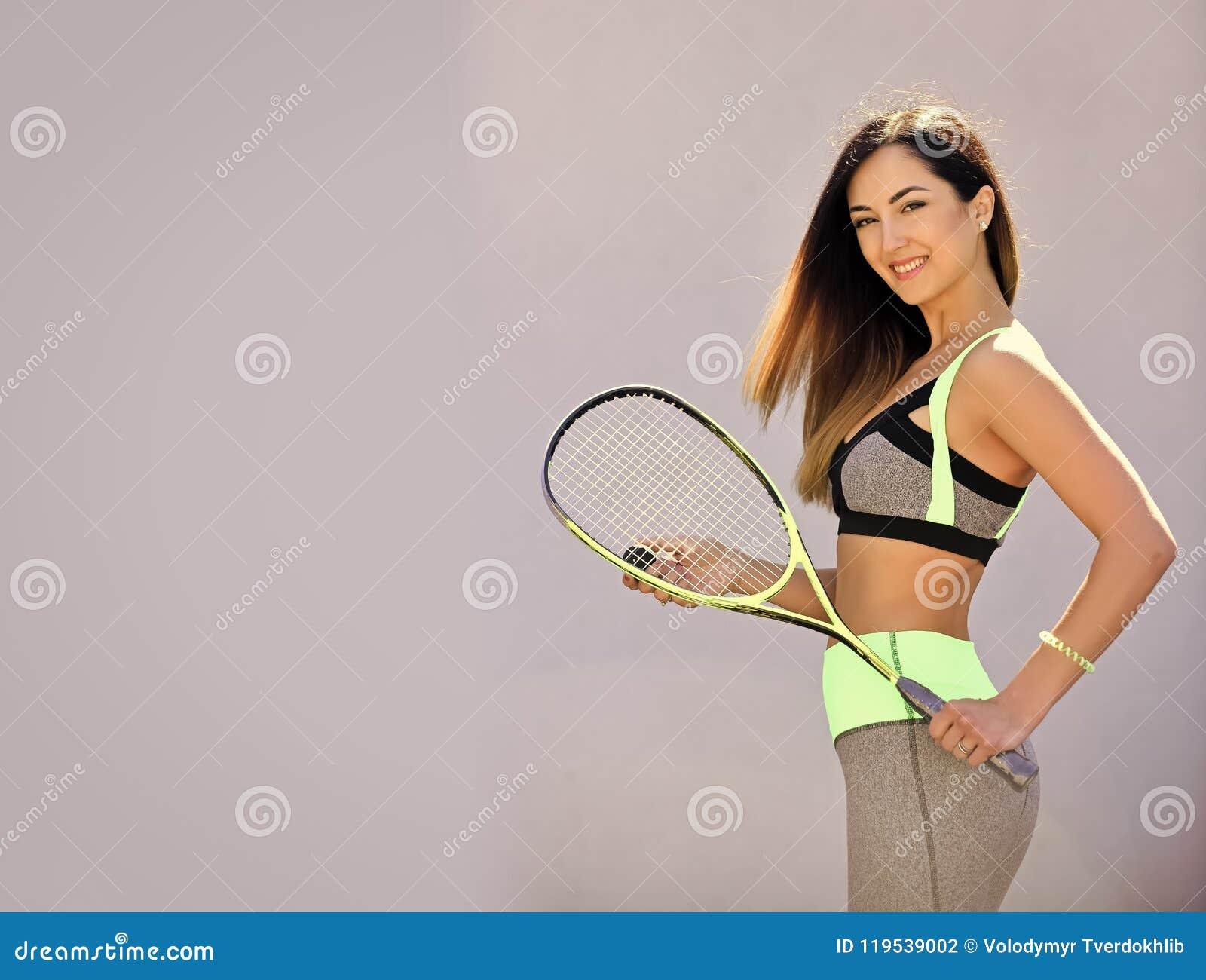 O jogo da dieta e do esporte, copia o espaço Mulher no sportswear com a raquete de polpa no fundo cinzento