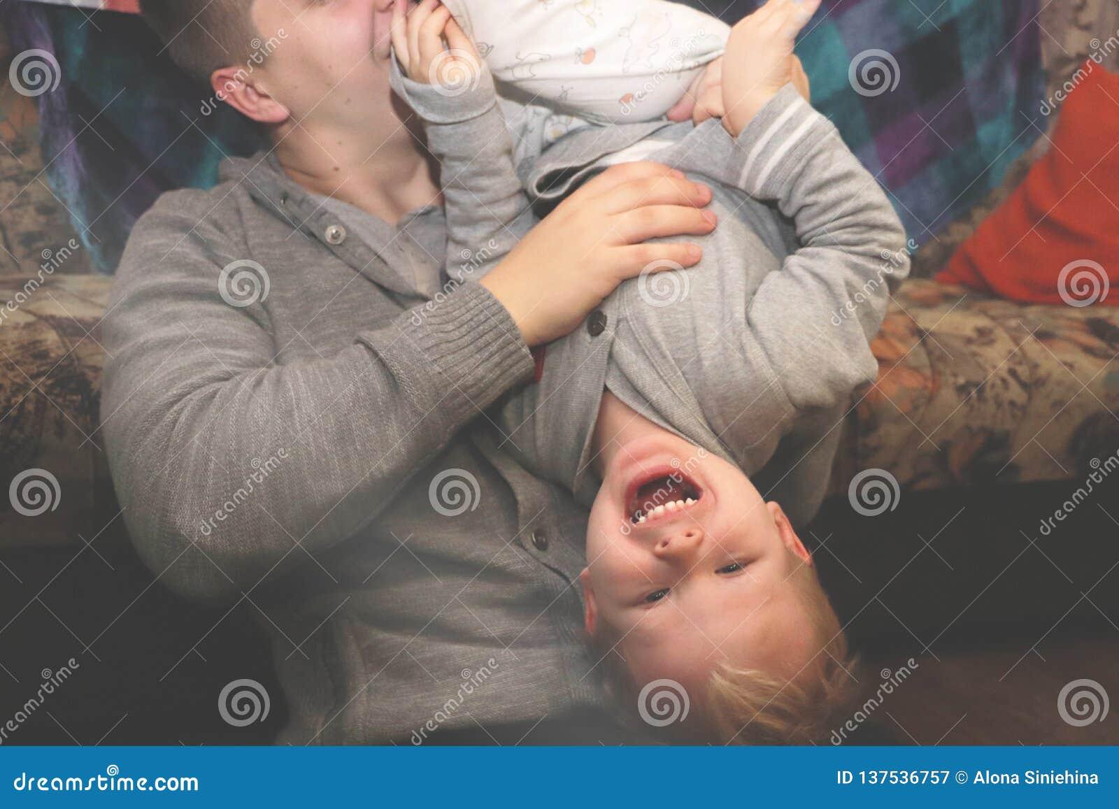 O jogo do paizinho e do filho, concede O pai girou seu filho de cabeça para baixo, os risos da criança
