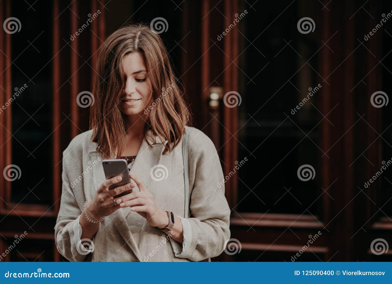 O jovem fêmea deleitado satisfeito olha o vídeo no telefone esperto, lê a notificação da operação bancária, vestida na capa de ch