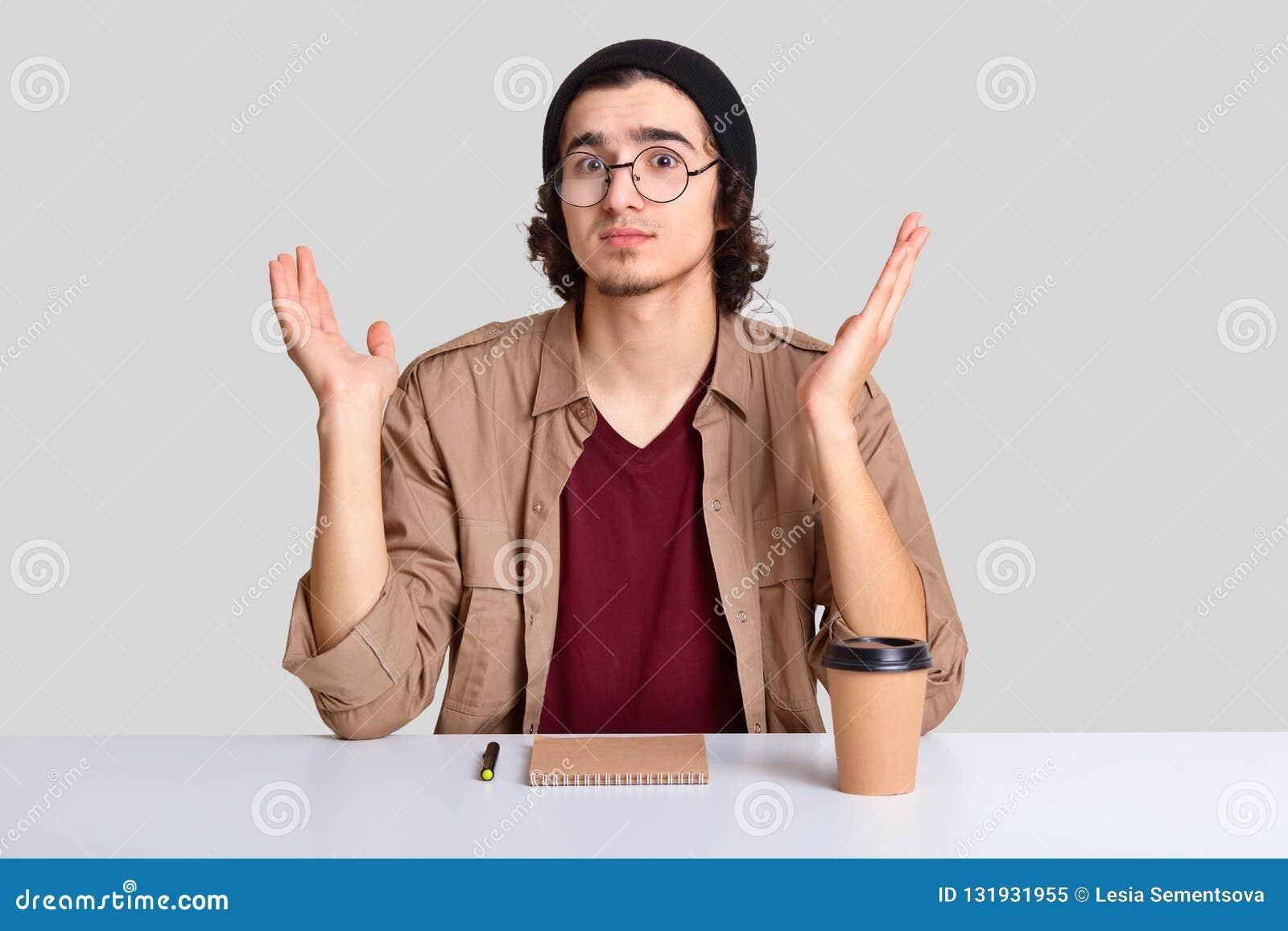 O jovem hesitante à nora espalhou as palmas com apatia, olhares com perplexidade, veste vidros óticos redondos, chapéu e a camisa