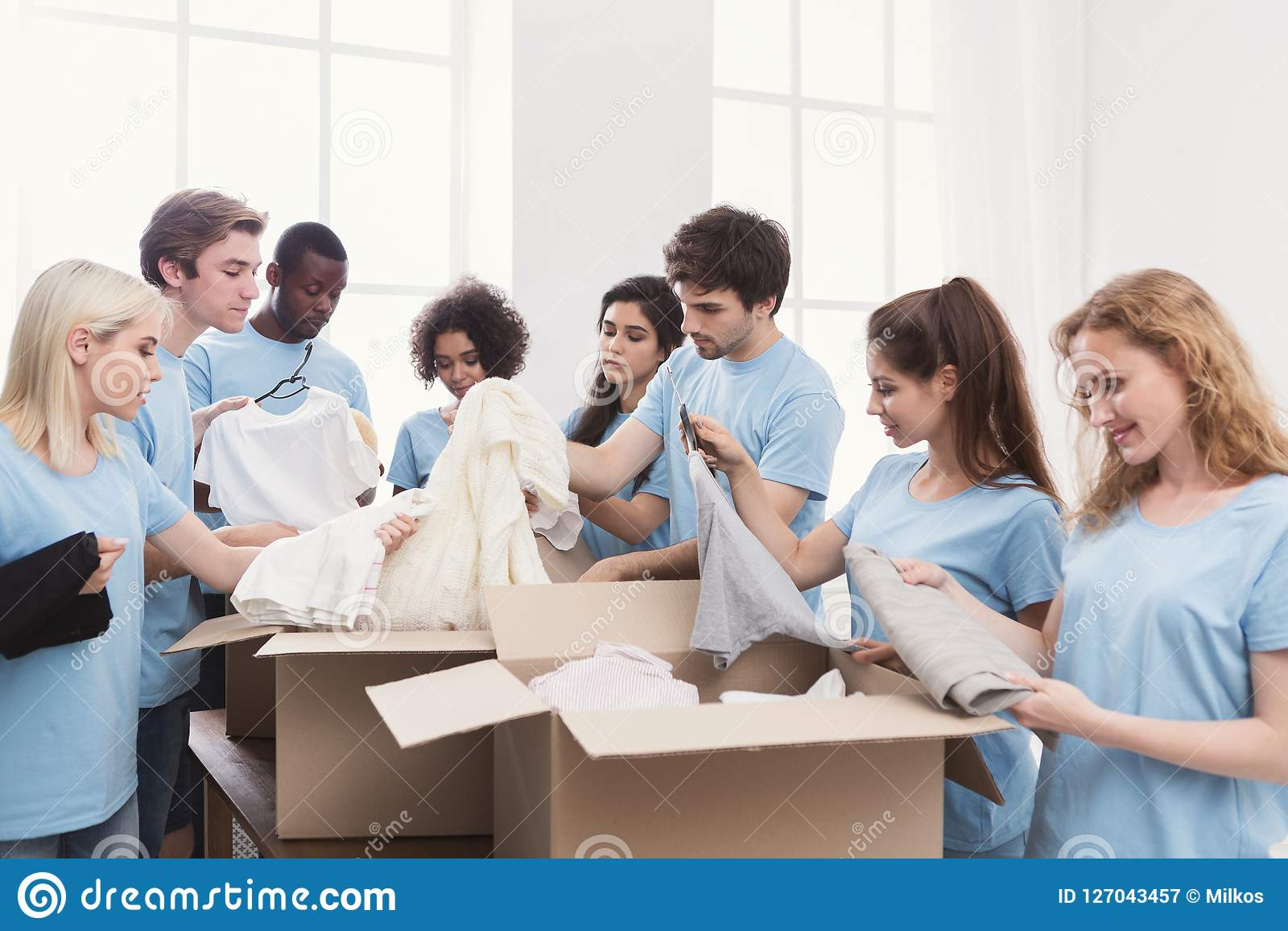 O jovem oferece o grupo que trabalha com doação da roupa