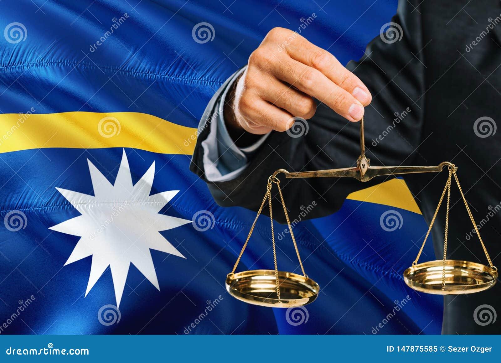 O juiz nauruano está guardando escalas douradas de justiça com fundo de ondulação da bandeira de Nauru Tema da igualdade e concei