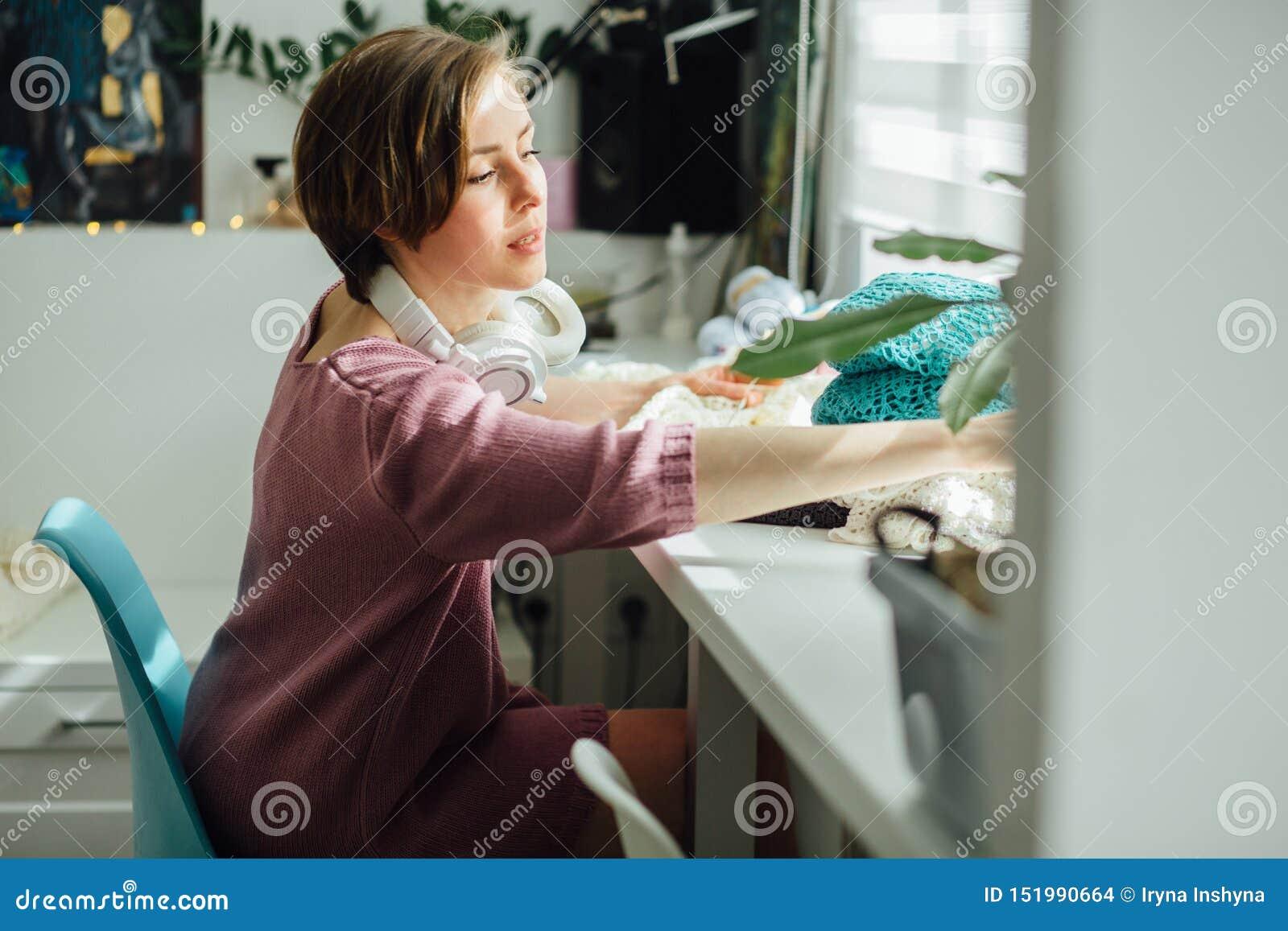 O lado do desenhista da mulher que faz malha o vestido macio com faz crochê no trabalho criativo do freelancer fêmea interior mod