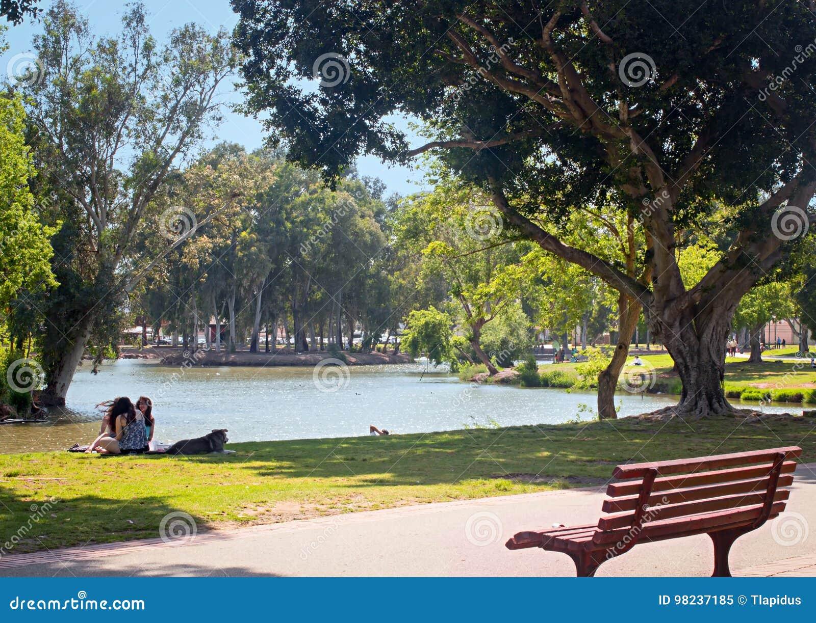 O lago, banco, meninas com cão, e relaxa no parque de Yarkon, Tel Aviv, Israel
