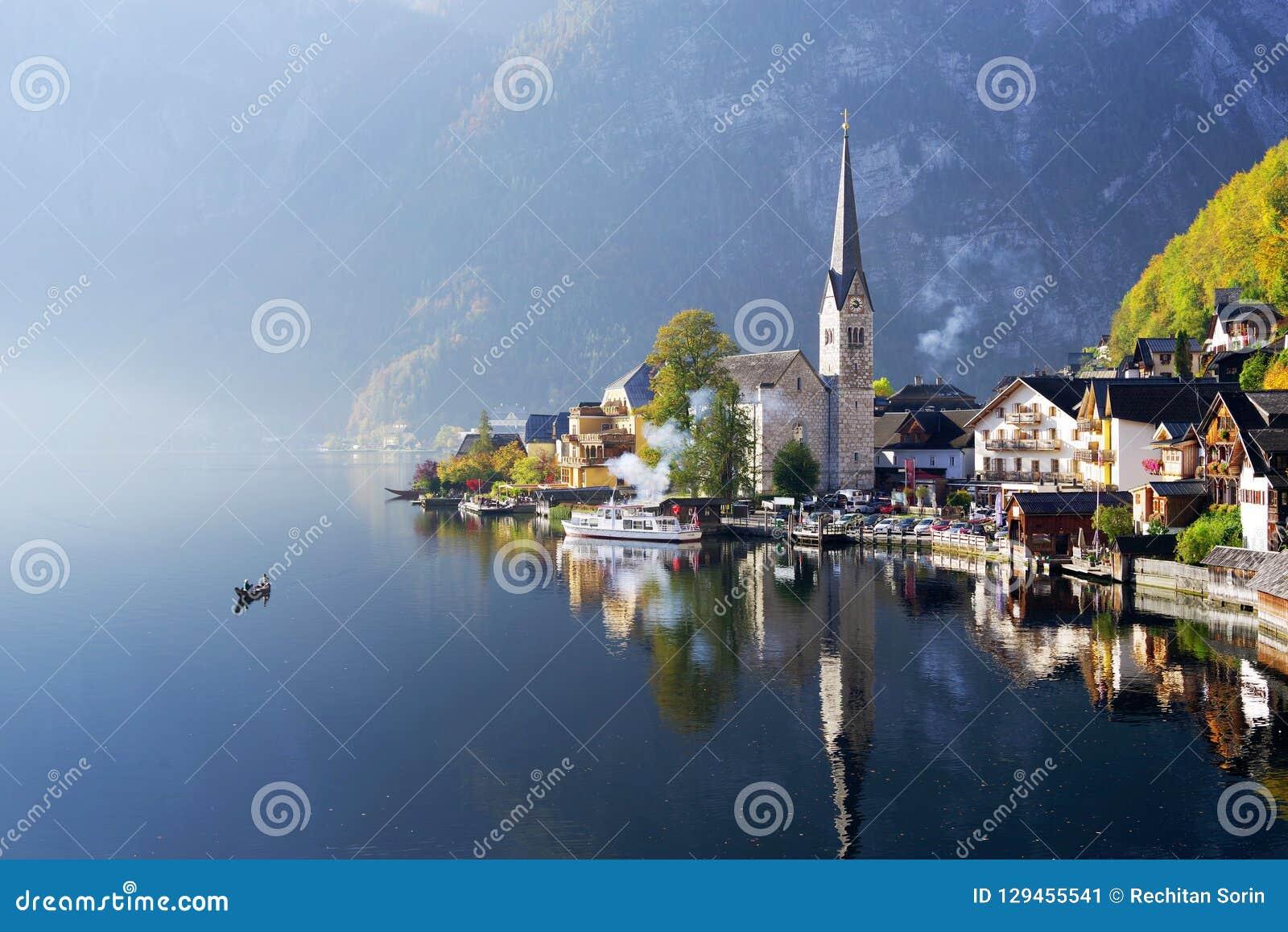O lago famoso Hallstatt em uma manhã nevoenta do outono