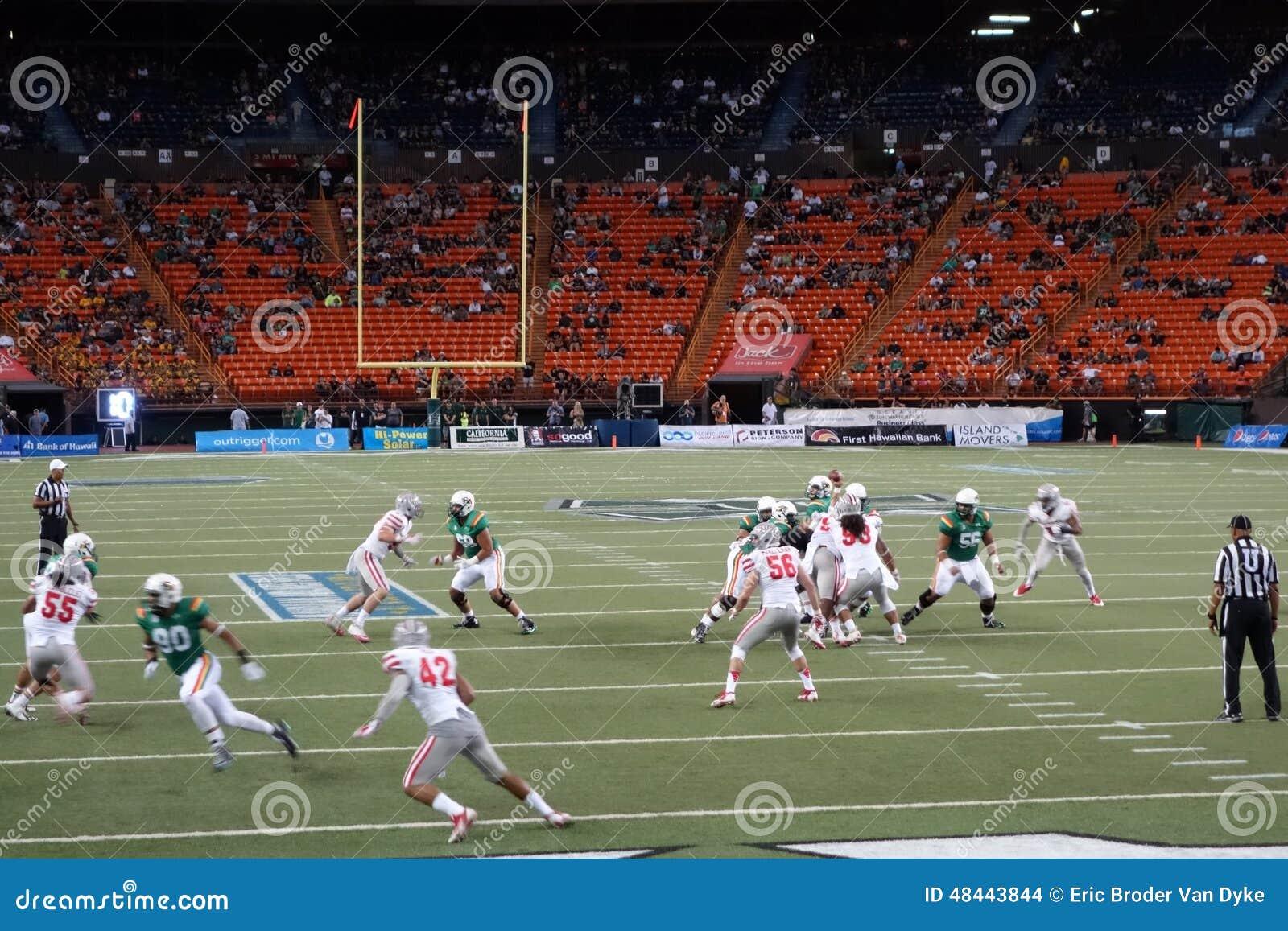 O lançador do UH ajusta-se para jogar a bola enquanto os jogadores escarafuncham para obter o ope