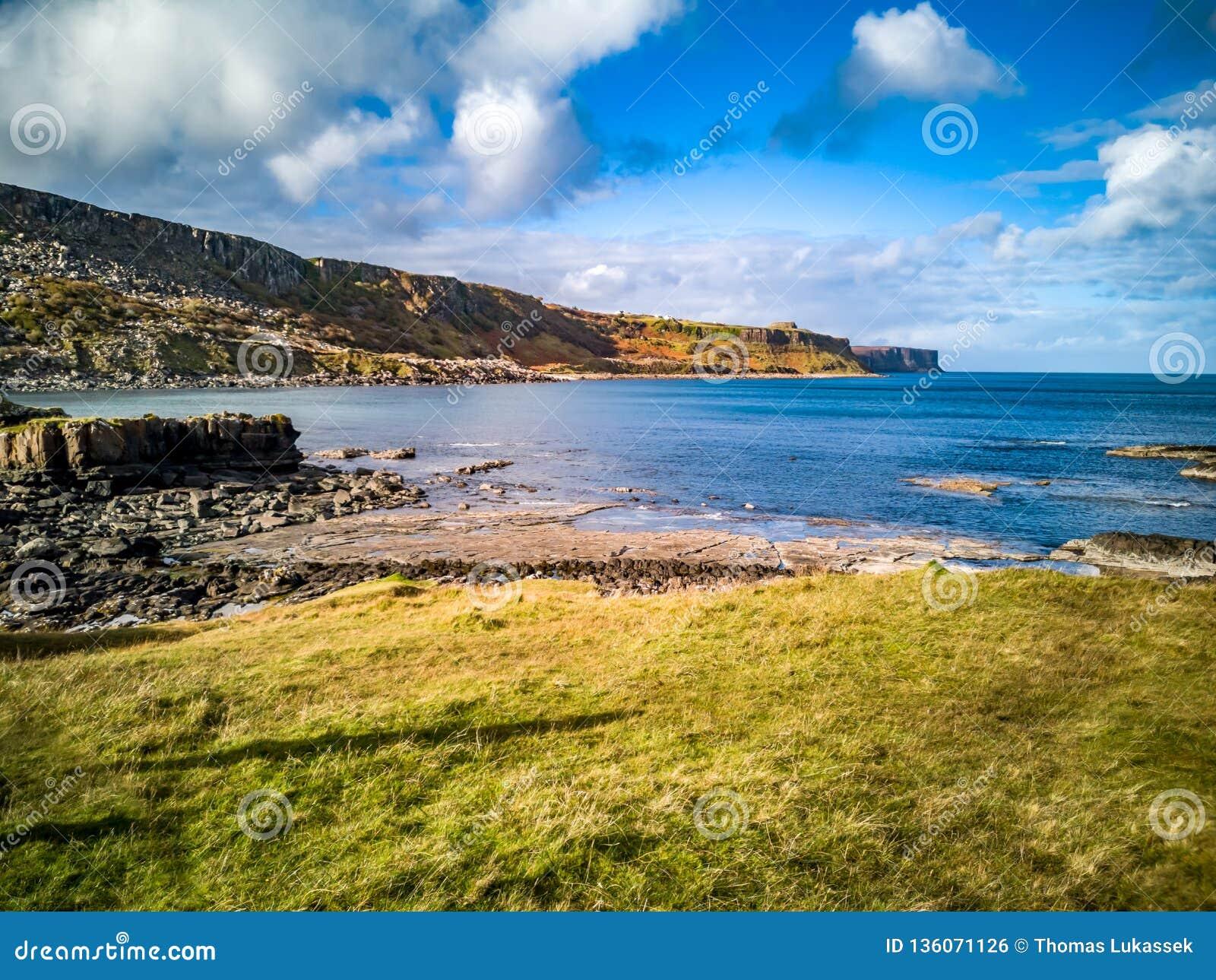 O litoral com as pegadas raras do dinossauro do tracksite sauropod-dominado do nam Brathairean de Rubha, irmãos