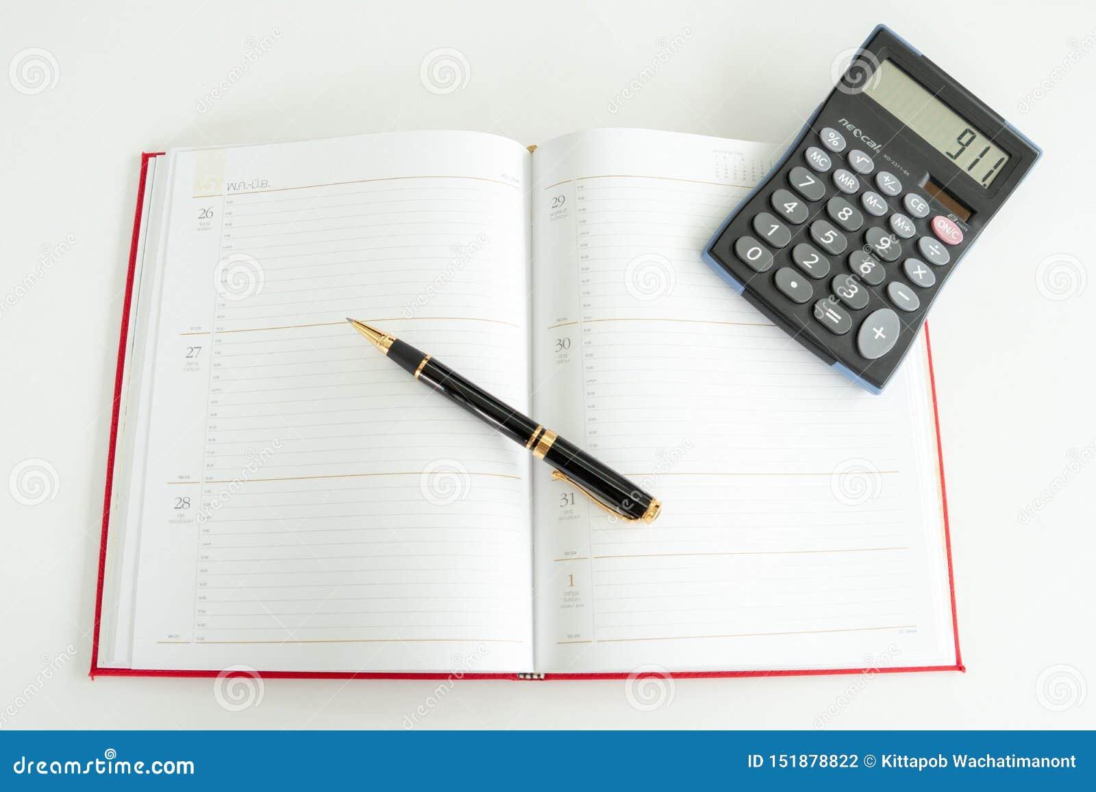 O livro diário do plano espalhou para fora com uma pena e uma calculadora de fonte nele