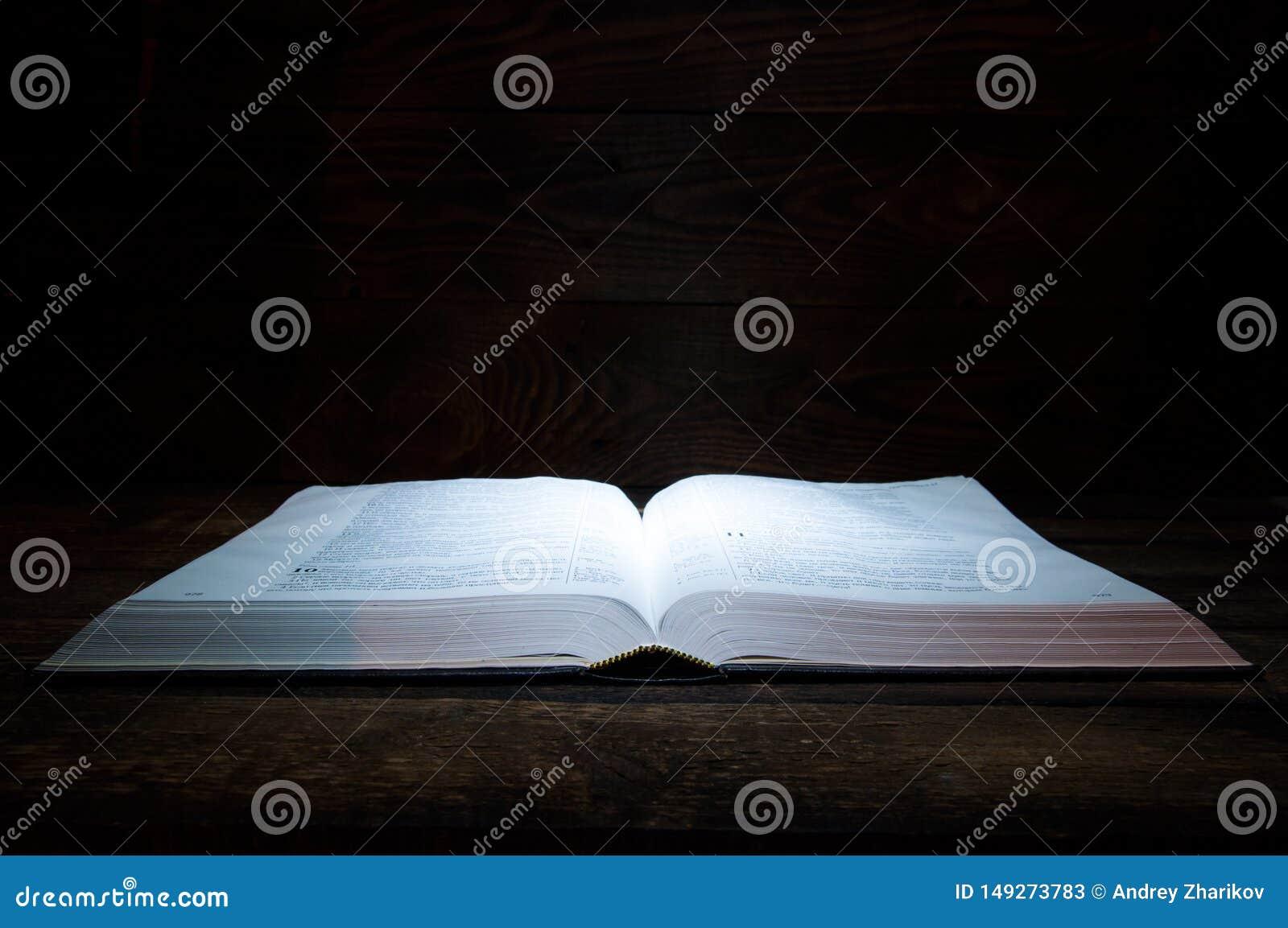 O livro grande das mentiras da B?blia em uma tabela de madeira Na obscuridade Uma luz brilha no livro de cima de