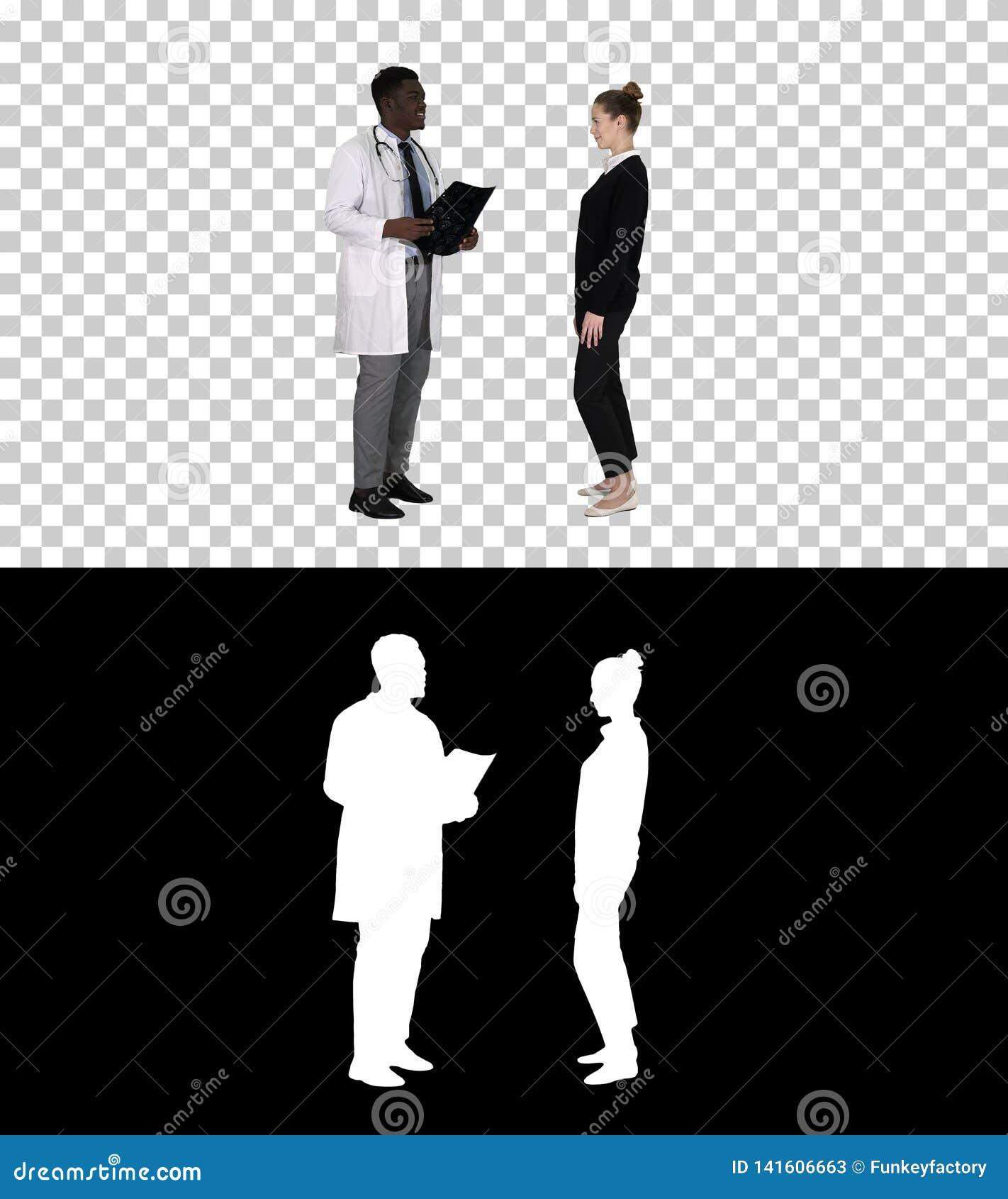 O médico que mostra a um paciente o raio X resulta então as folhas pacientes, Alpha Channel