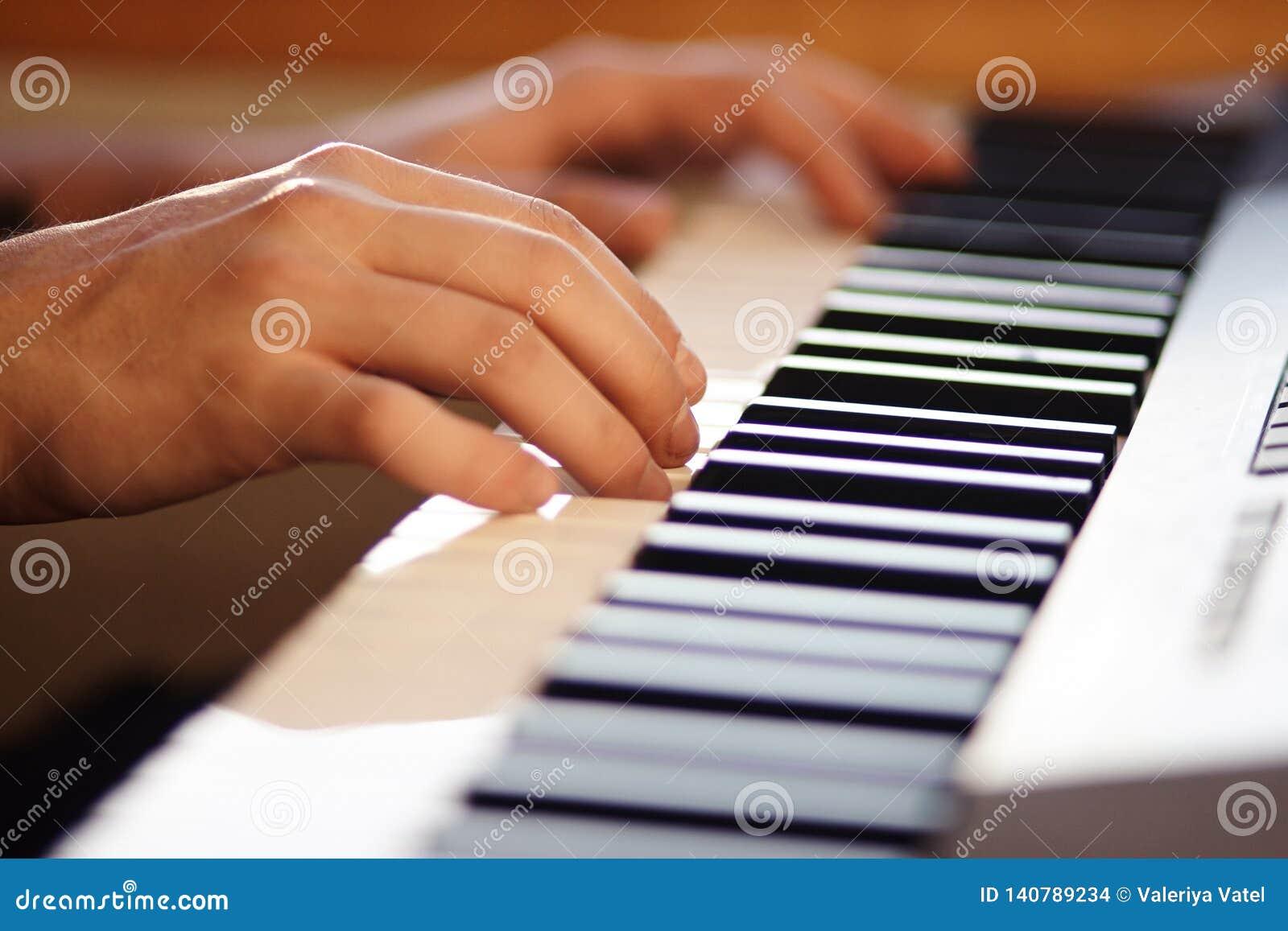 O músico que pressiona as chaves de um sintetizador musical moderno