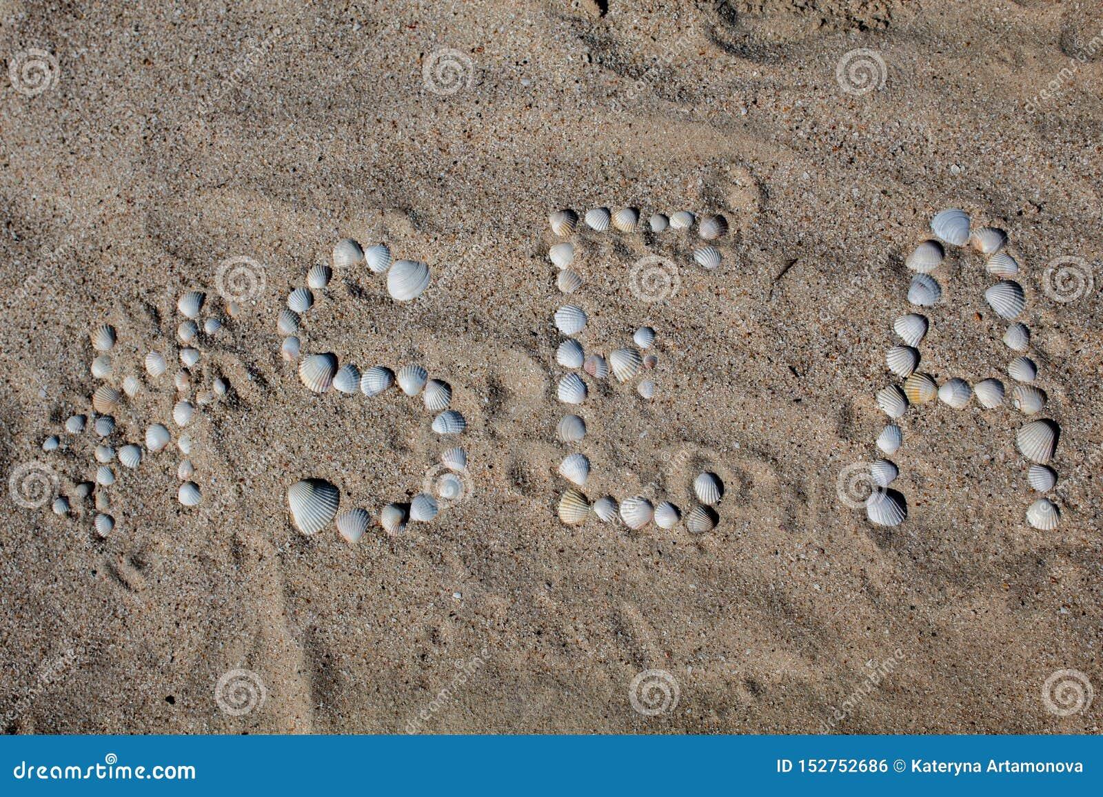 O mar da palavra no inglês, apresentado na areia com escudos