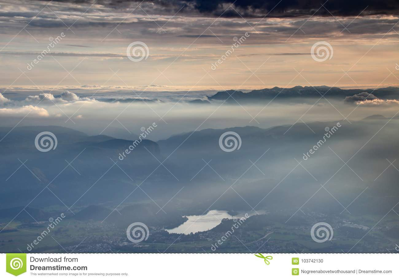 O mar das nuvens, da névoa e do sol irradia no por do sol, lago sangrado, Eslovênia