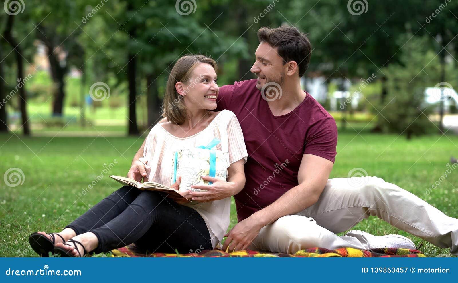 O marido de amor que dá a caixa de presente à esposa, apresenta para nenhuma razão, amor verdadeiro