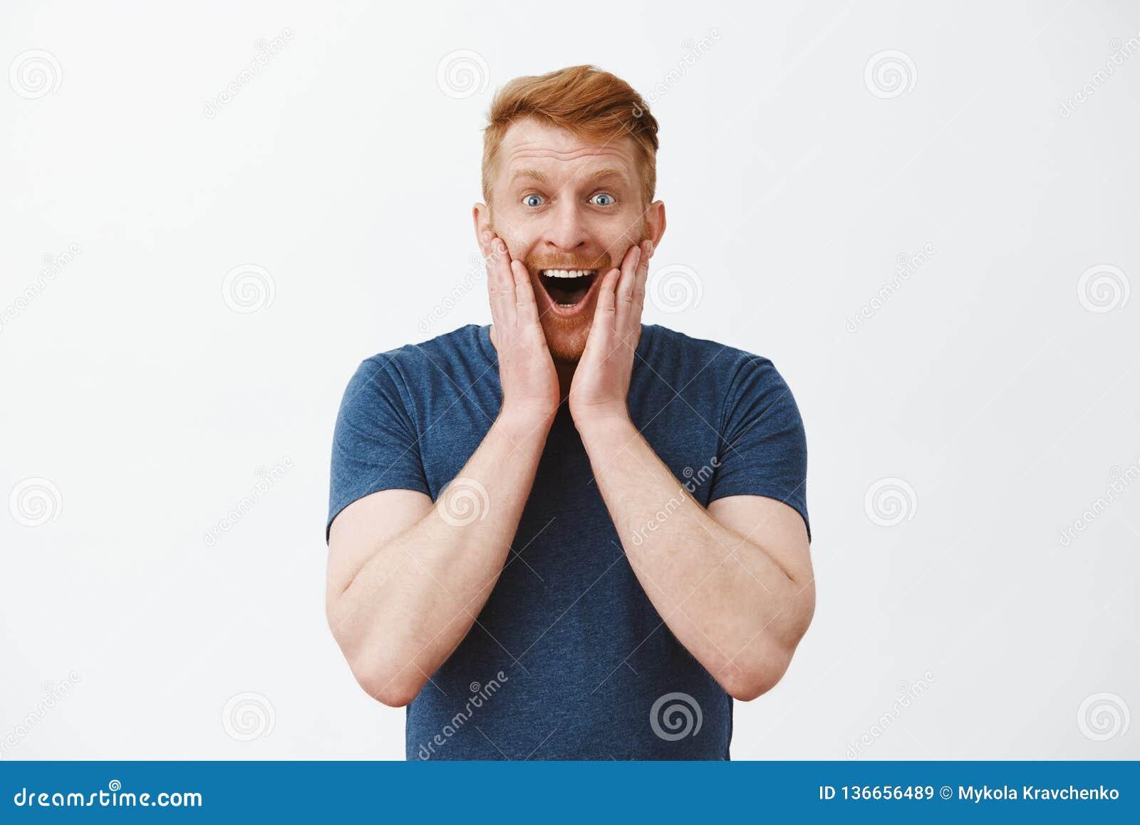 O marido encontrou a esposa grávida, sendo feliz e excitado Homem atrativo alegre do ruivo com a cerda, guardando as palmas sobre