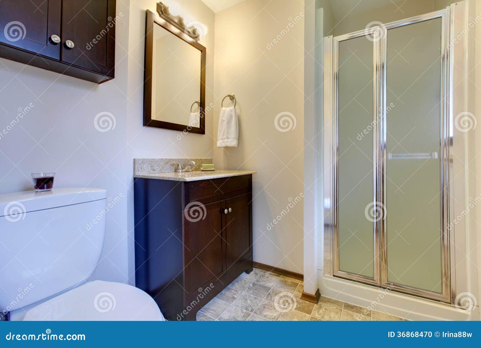 Banheiro elegante com os armários do marrom escuro e o assoalho de  #654627 1300x957 Banheiro Amarelo E Marrom