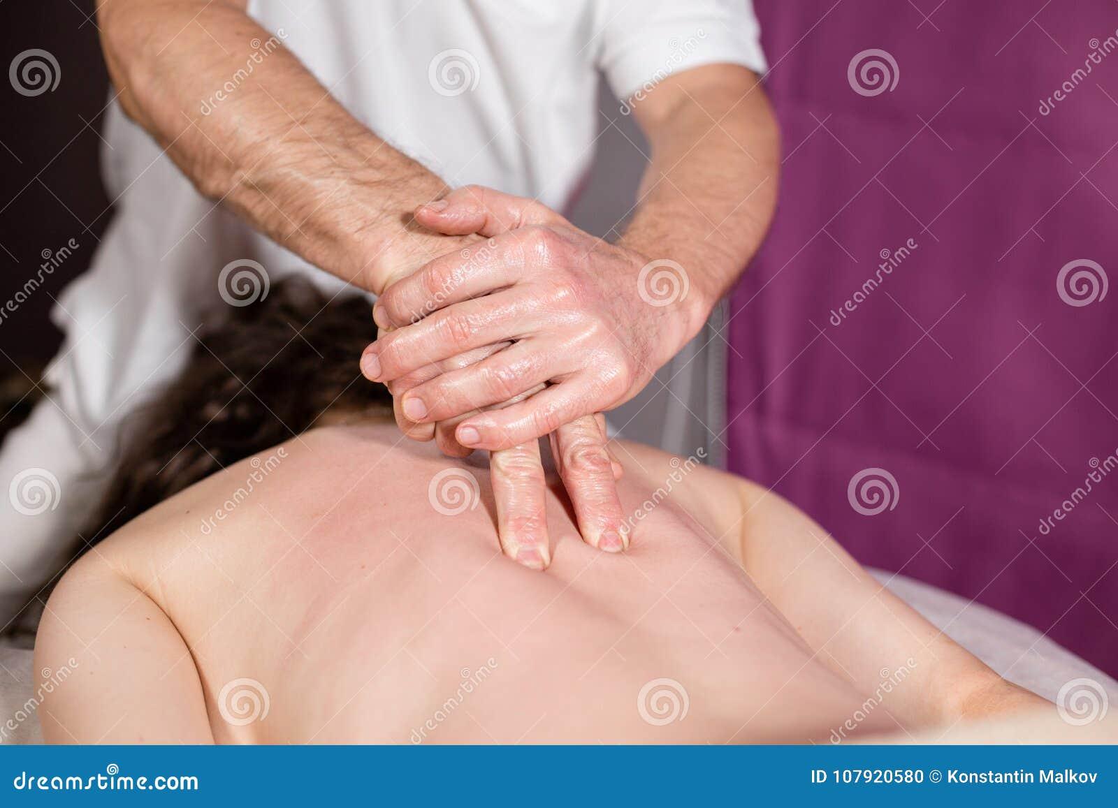 O massagista entrega fazer a espinha e massagem traseira, pescoço e mão O paciente relaxado aprecia Mãos do homem que fazem massa