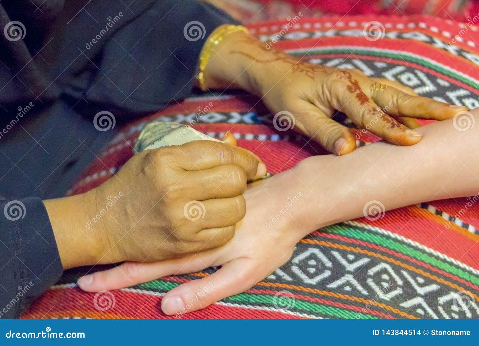 O mehndi mestre tira a hena em uma m?o f?mea