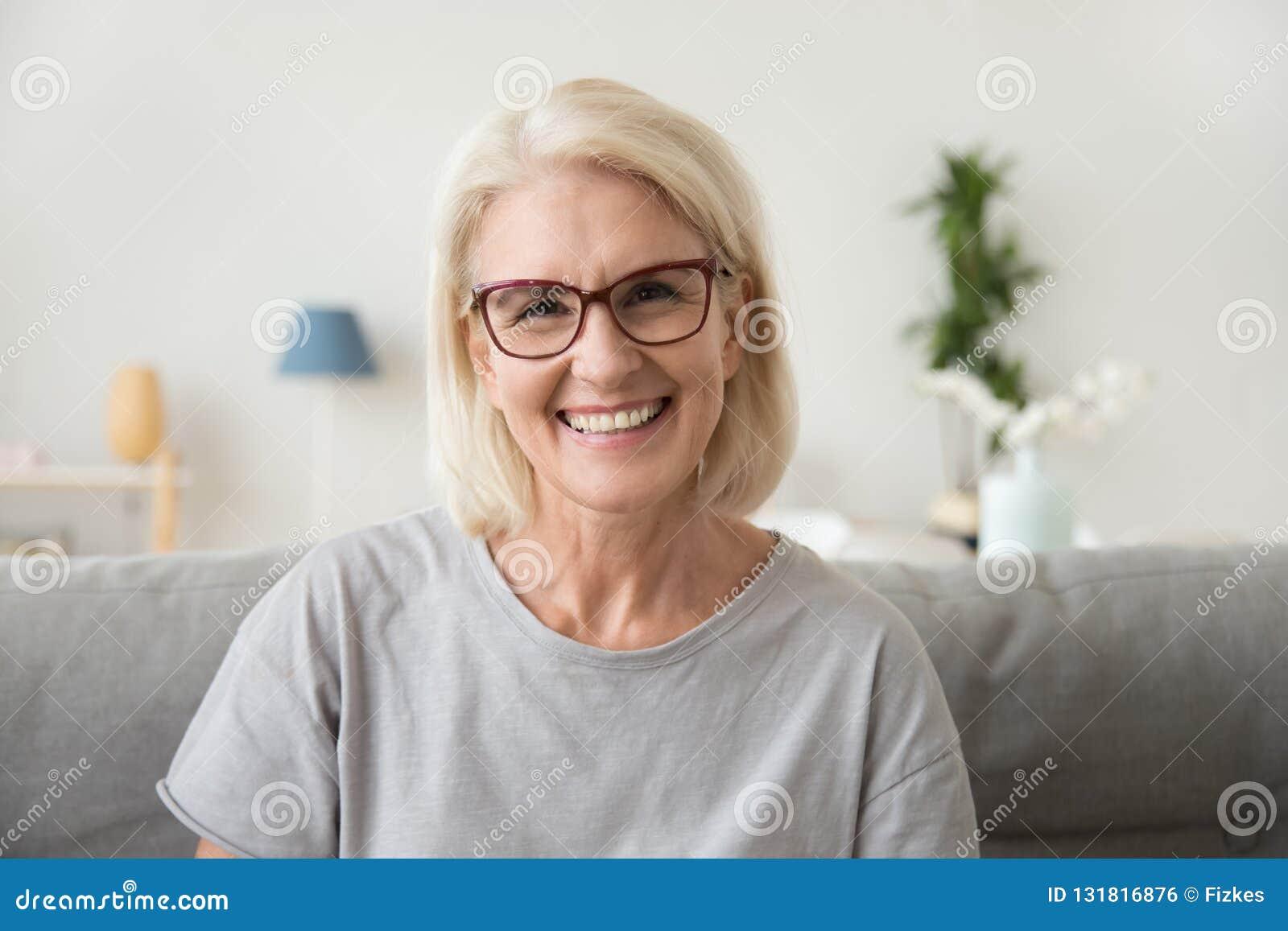 O meio de sorriso envelheceu a mulher de cabelo cinzenta madura que olha a câmera