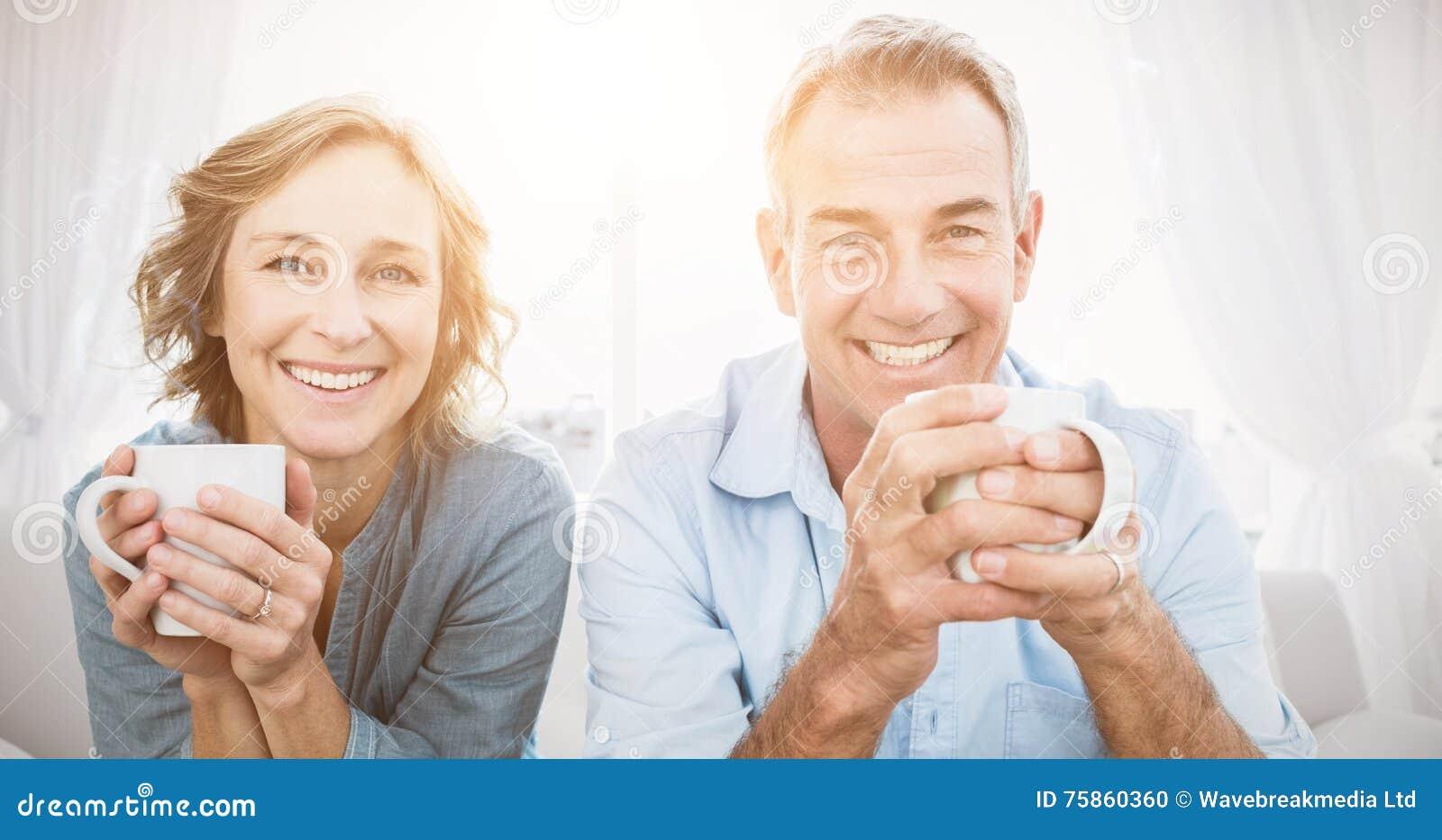 O meio de sorriso envelheceu os pares que sentam-se no sofá que come o café