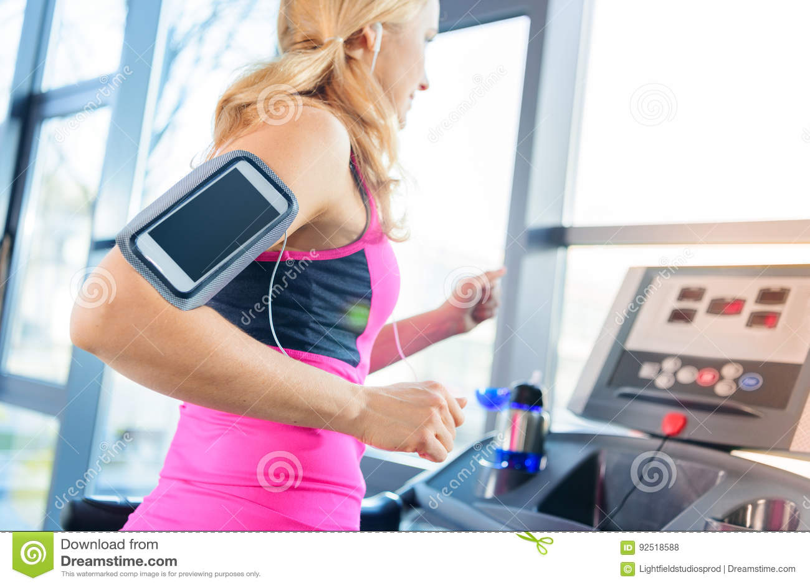 O meio envelheceu a mulher no treinamento do sportswear na escada rolante no gym