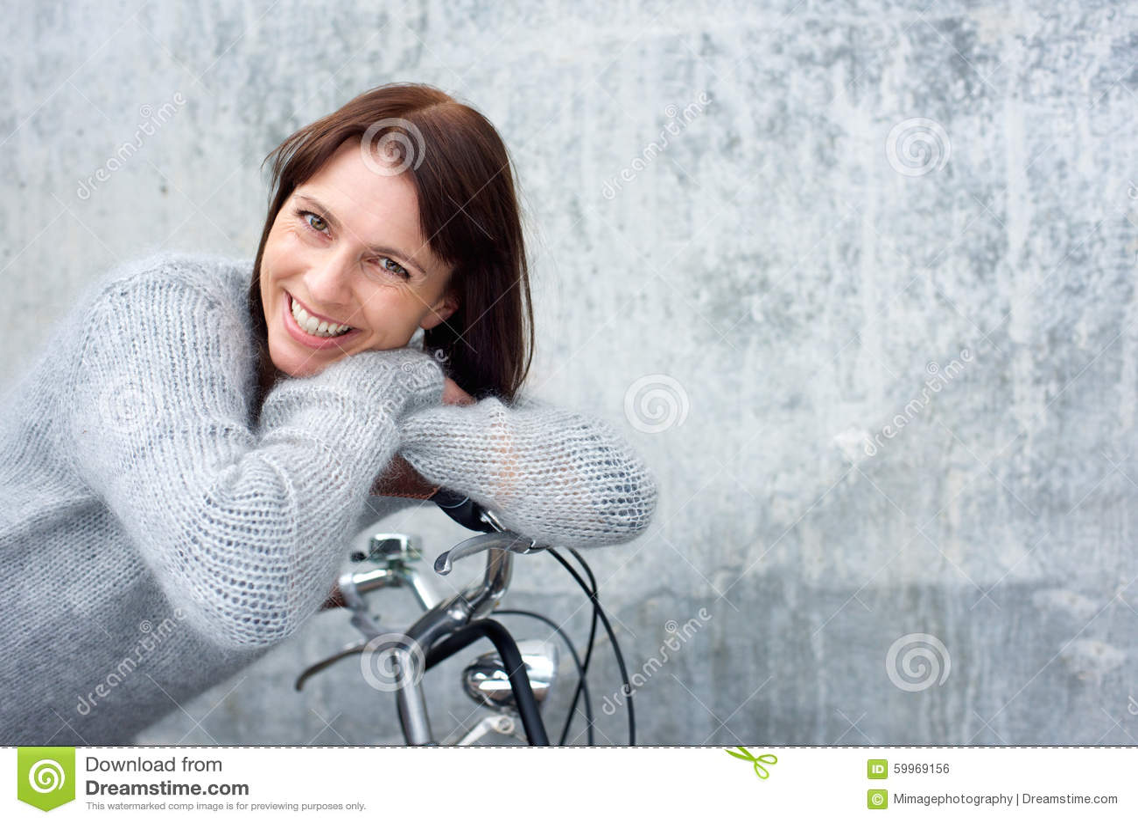 O meio envelheceu a mulher que sorri e que inclina-se na bicicleta